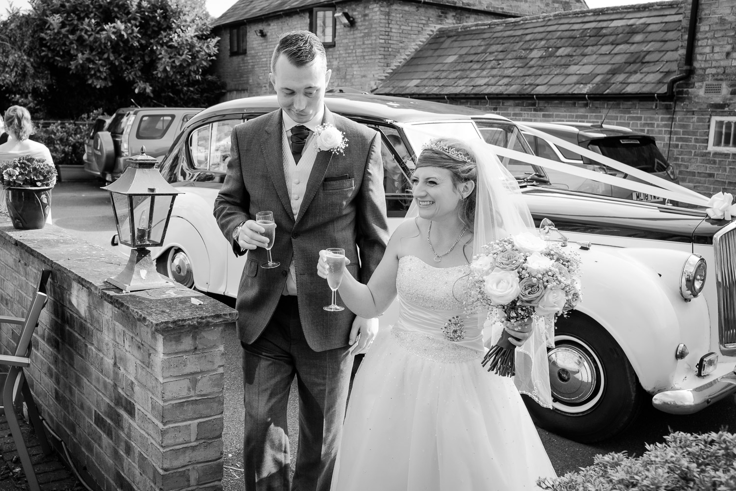 Newlyweds celebrate as they arrive at their reception venue Ruddington Country Cottage