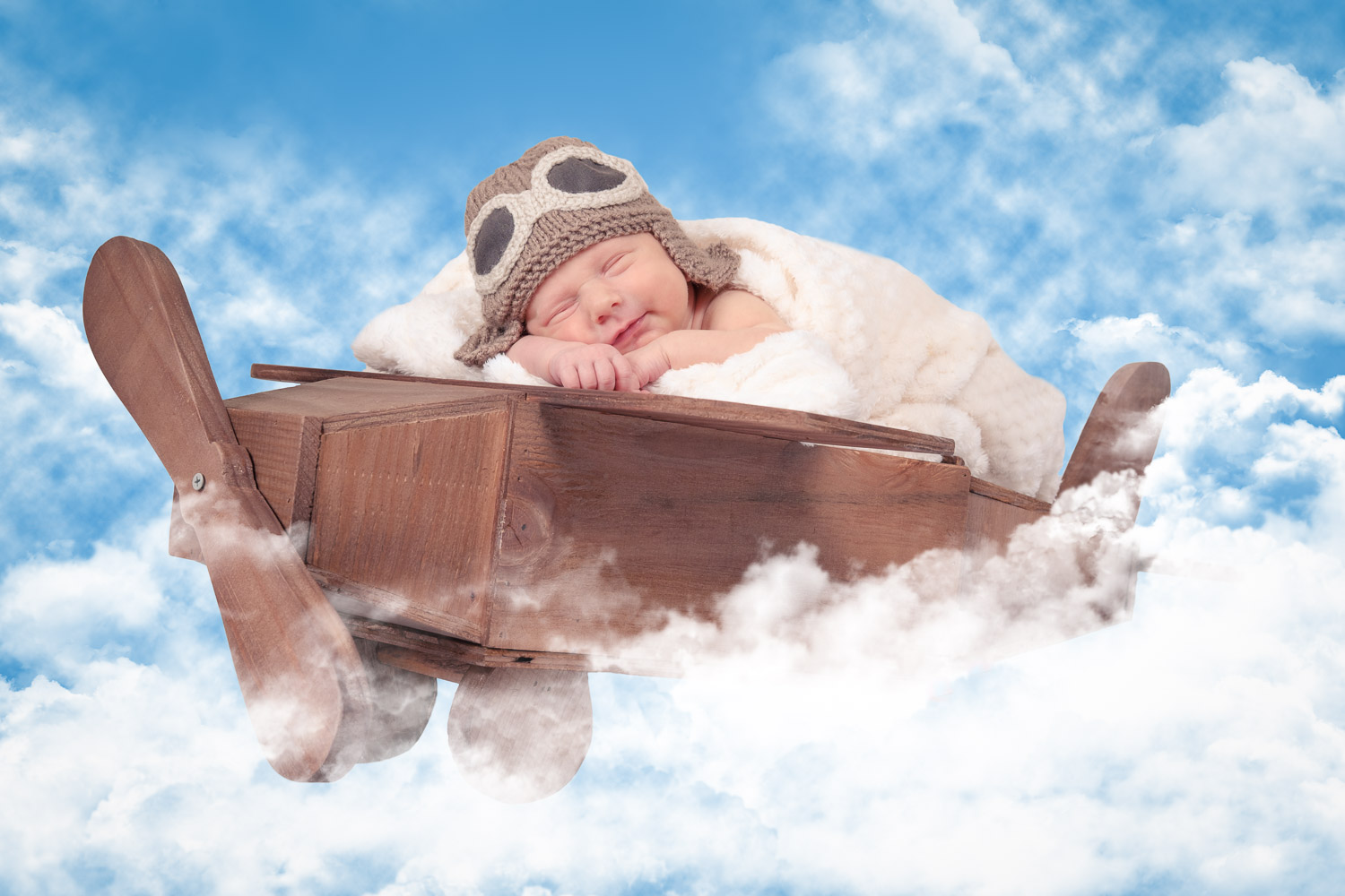 Newborn sleeping in a model aeroplane with pilot hat. Creatively flying in the sky.