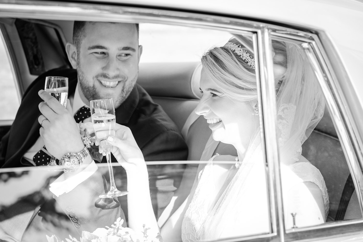 West Bridgford, Nottingham - bride and groom celebrating with a glass of Champaign in their wedding car