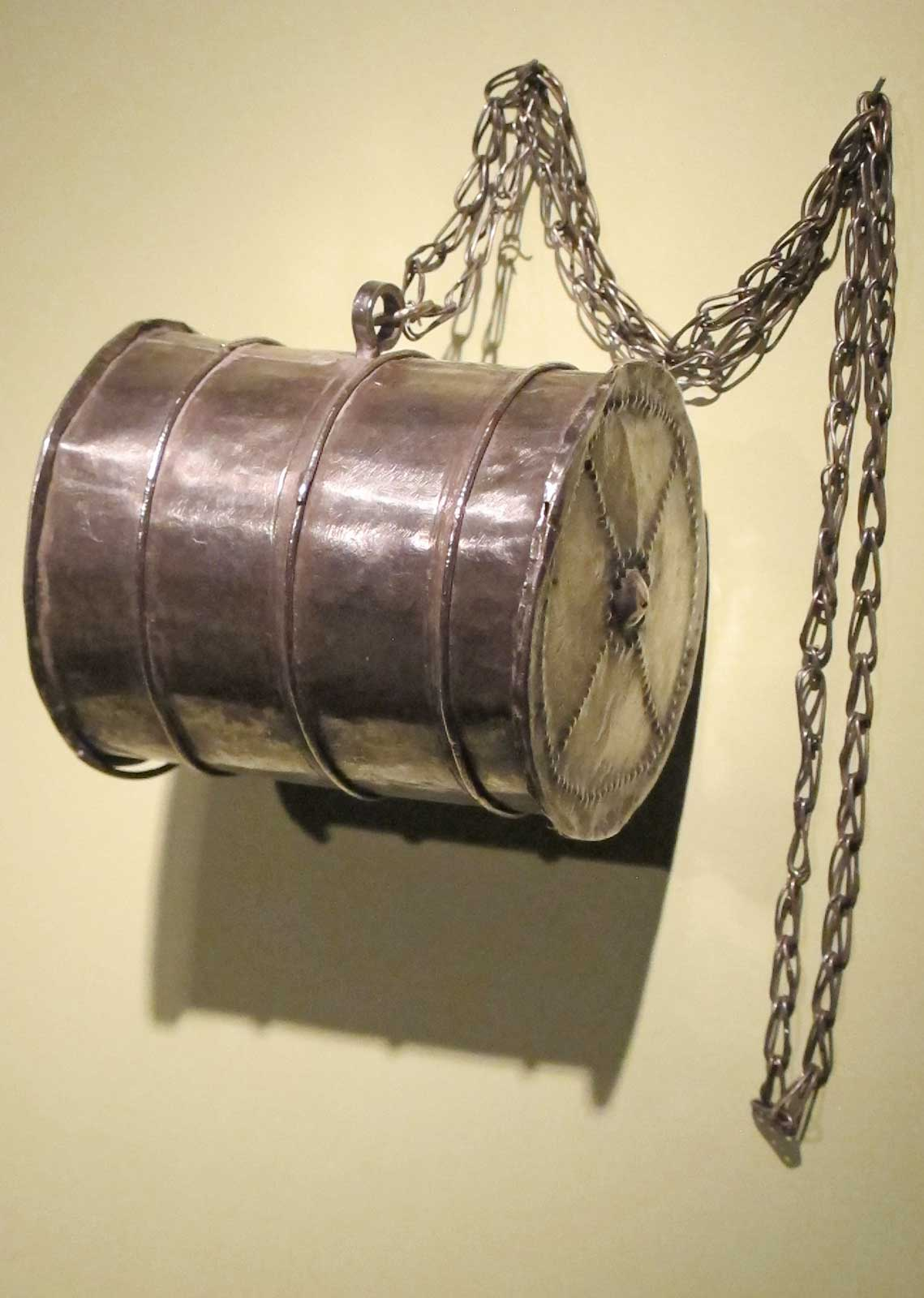 Barrel-shaped pendant by Mende artist, Sierra Leone, of metal, early 20th century.