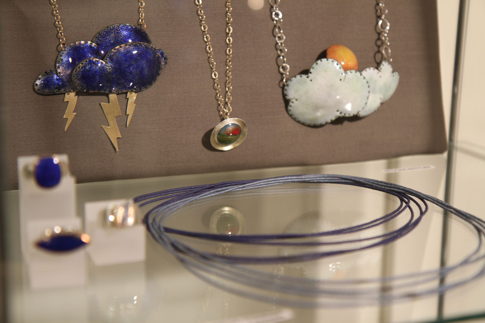 Lightning and thunderclouds, with a touch of sun, adorn Brooke Battles' enamel pendants.