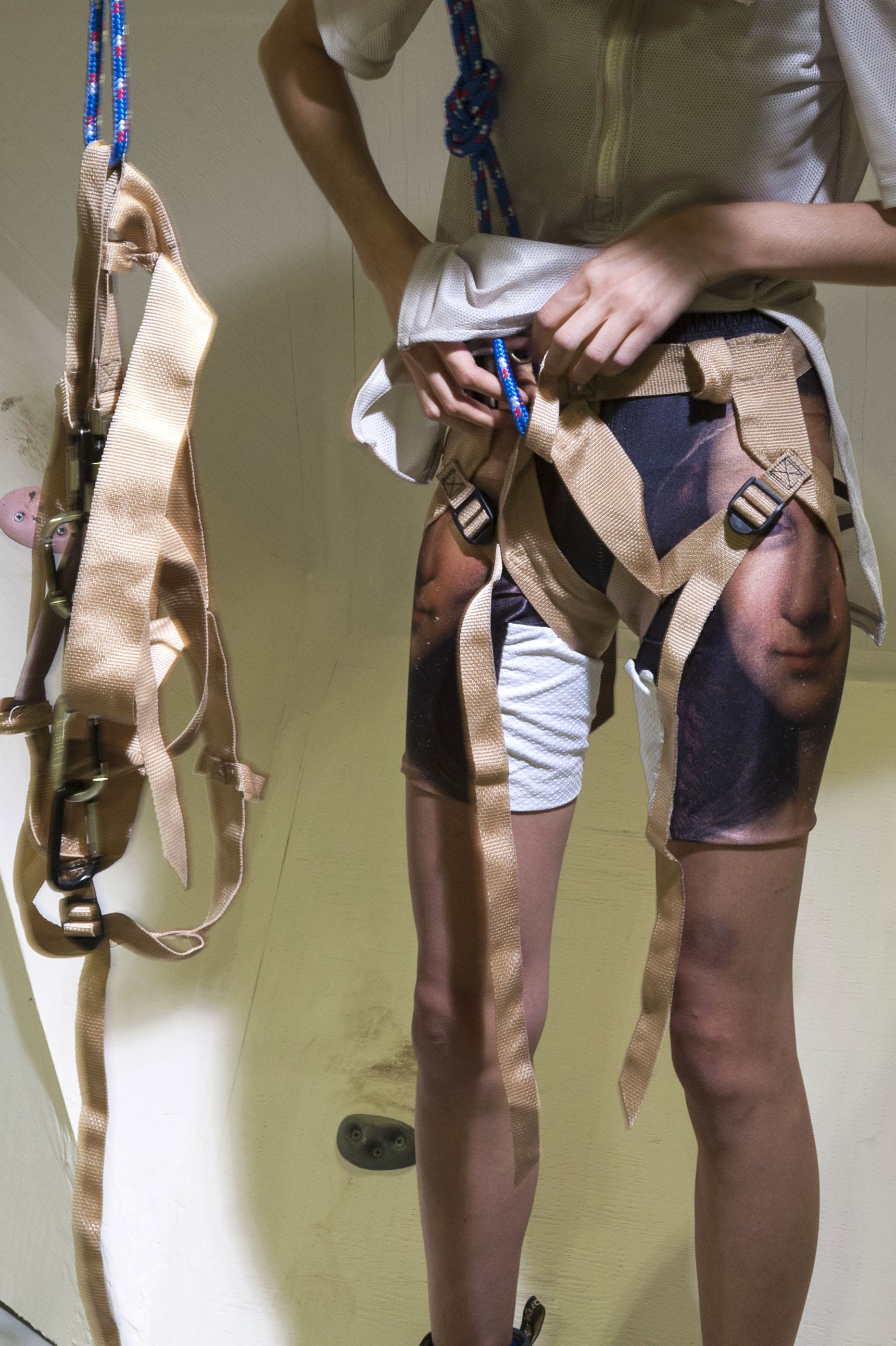 Kim interacting with the belay system wearing personalized climbing attire.