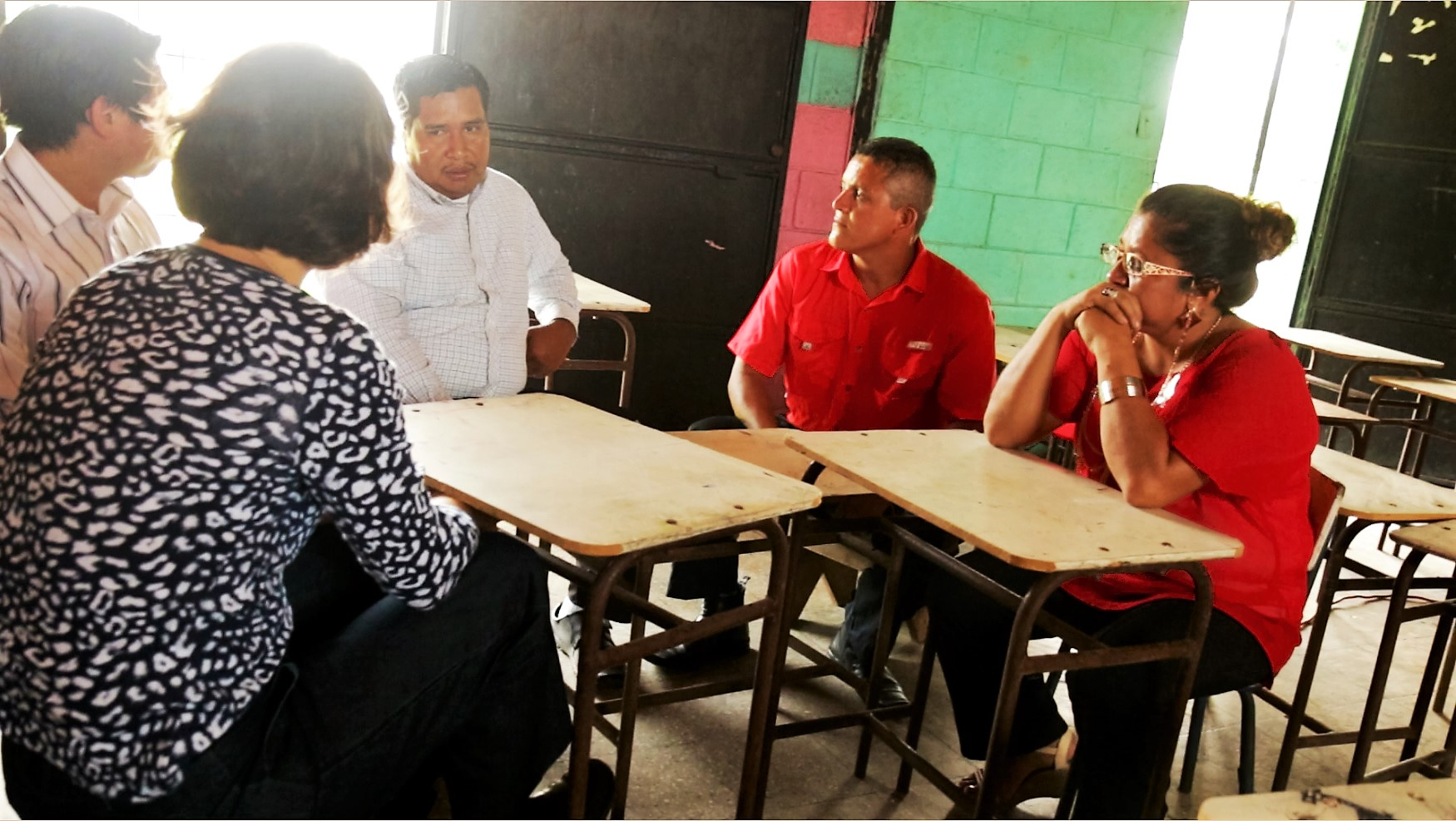 Cesar and Emma discussing progress with teachers and school principal.