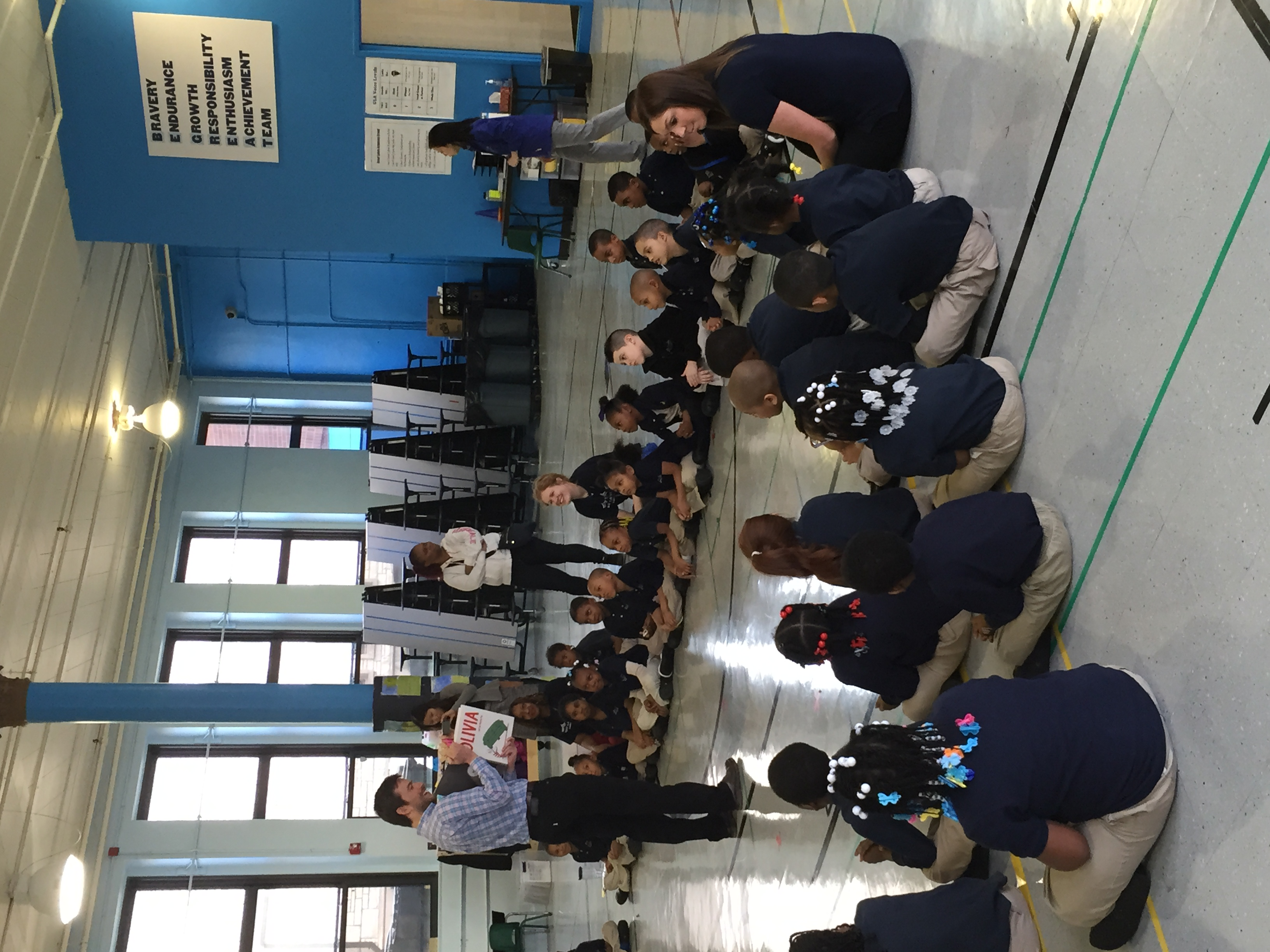 Booth-Ed co-chair Jesse Feinberg reads to students at Great Lakes Academy's weekly community celebration.
