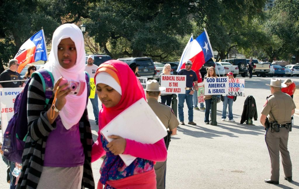 Amina Hassan, left, 11, of Grand Prairie, and Ayefa Klair, 10 of Irving, are faced with anti-Muslim protesters at the Texas Muslim Capitol Day in Austin, Texas. Photo: Jay Janner, Associated Press