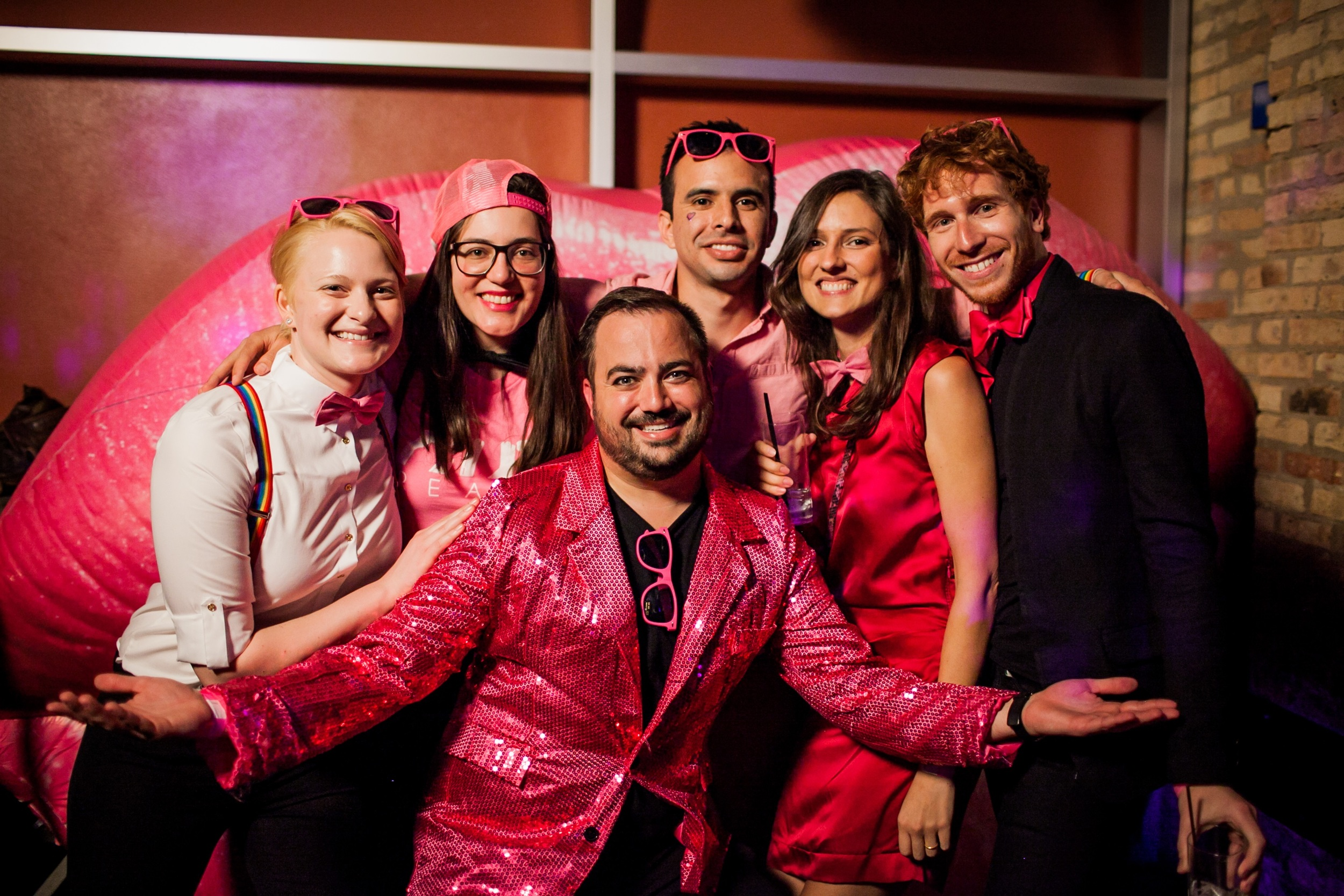 Booth OUTreach co-chair and project leader, Erik Underwood (center), strikes a pose with his fellow co-chairs in front of the signature pink lips at OUTreach's annual #PinkParty at Sidetrack Video Bar in Boystown.