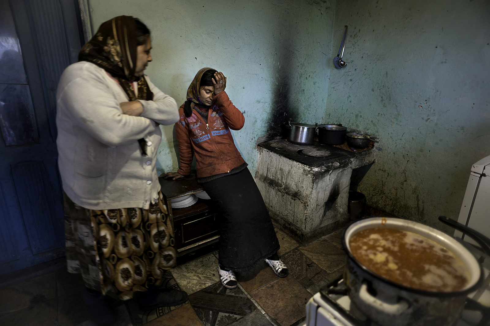 Complaining of stomach pains Viorica Gulie, 31, takes a break from cooking soup for her family as her mother-in-law Constanta Gulie, 58,  looks on at left.  She suffers from Gastritis of her stomach.  With no money for medication or to go to the hospital she has to live in pain. Their house which has no running water or a bathroom is built on state land and they don't have title deeds so they are in fear of being evicted.  Photo taken in Slatina, Romania.©  Renée C. Byer