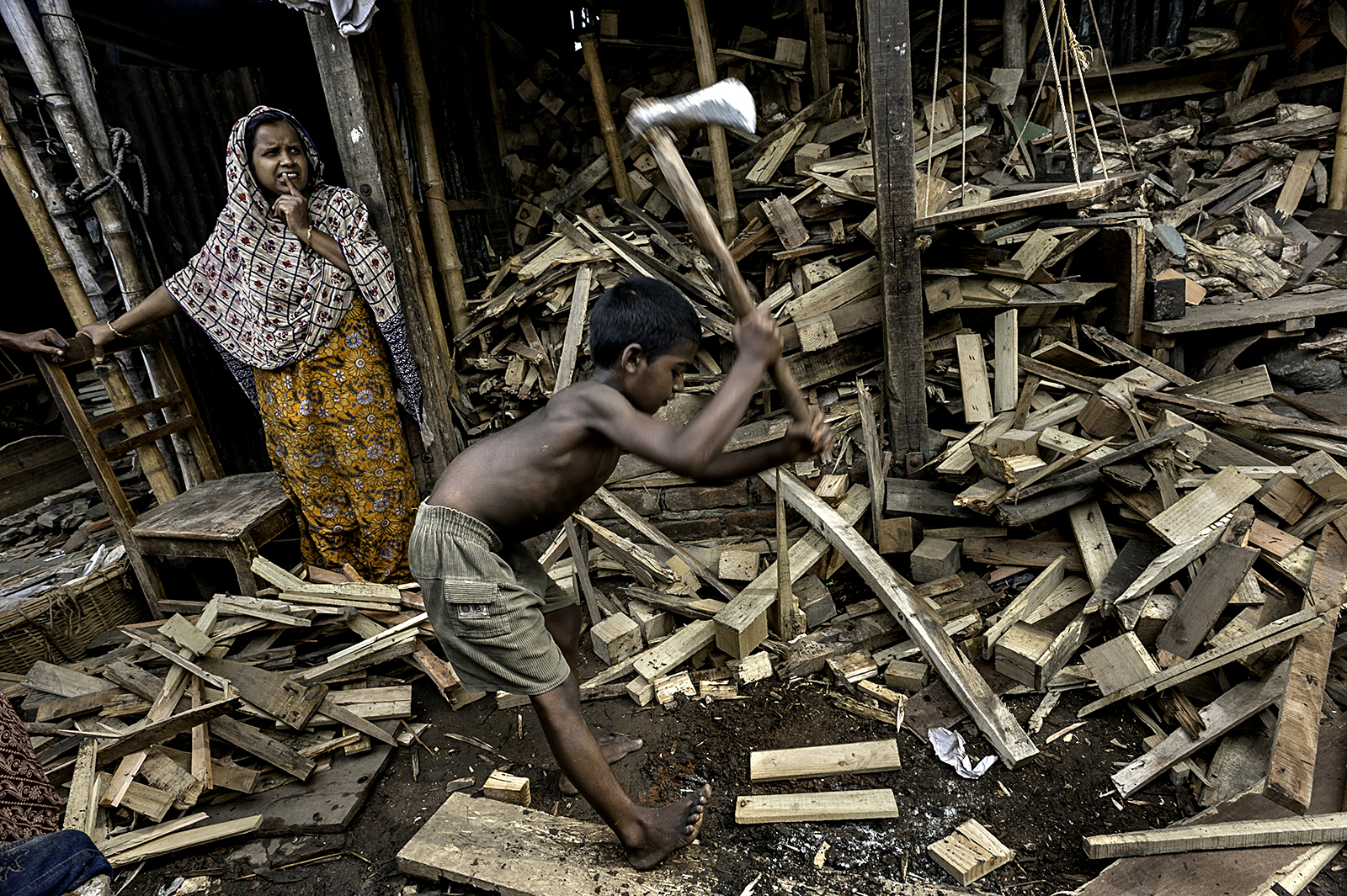 In another area of Bangladesh, Saiful, 9, works splitting wood without shoes or any kind of protective gear. Few children who work as he does are given any rights in the workplace, for legally they are too young to be working at all. ©  Renée C. Byer