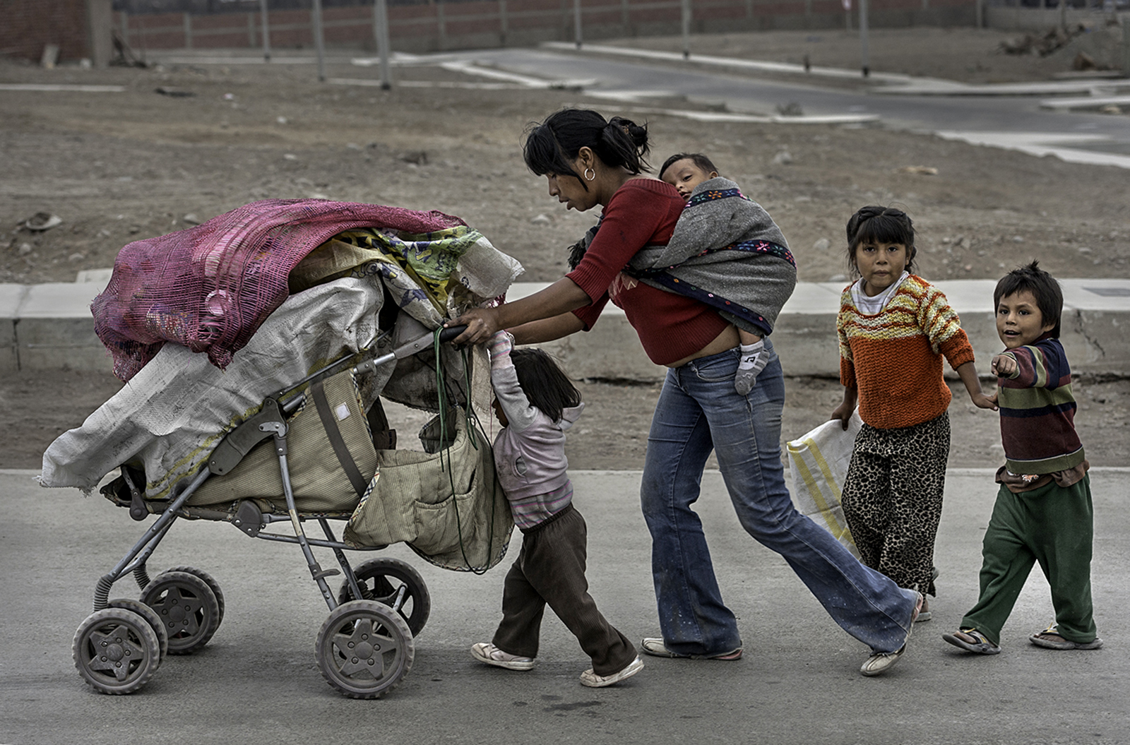 A victim of Domestic violence Erika Gonzales, 36, forms a train like procession as she walks with three of her children as well as her grandchild fastened to her back through the streets of Lima, Peru, collecting recyclables. In Lima, 20 percent of all its waste is gathered up in this manner. Her children are needed to help her and do not attend school.The family lives in a room with no running water or bathroom on the verge of eviction.©  Renée C. Byer