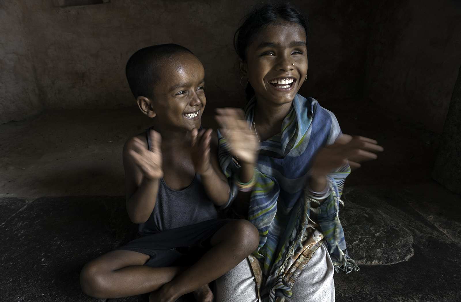 Hunupa Begum and her brother Hajimudin Sheikh, 6 resort to singing and clapping their hands to play and in the process make each other laugh. © Renée C. Byer
