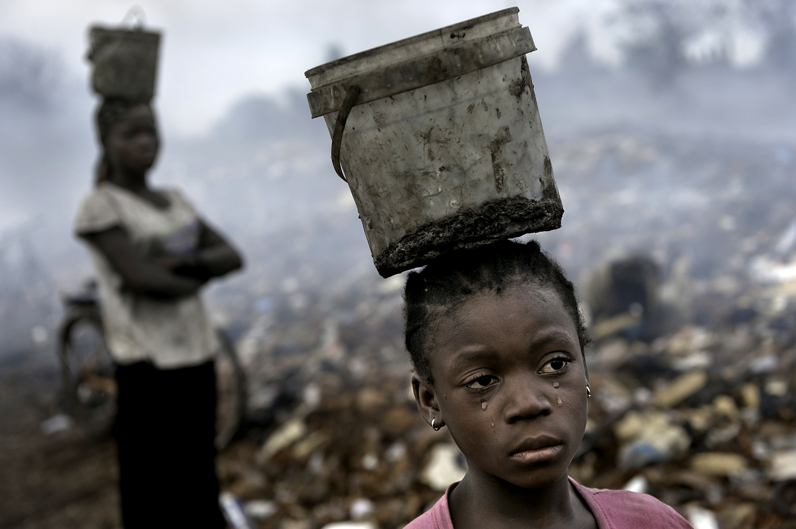 In Ghana in an e-waste dump that kills nearly everything that it touches, Fati, 8, works with other children searching through hazardous waste in hopes of finding whatever she can to exchange for pennies in order to survive. While balancing a bucket on her head with the little metal she has found, tears stream down her face as the result of the pain that comes with the malaria she contracted some years ago. This is work she must do to survive. ©   Renée C. Byer