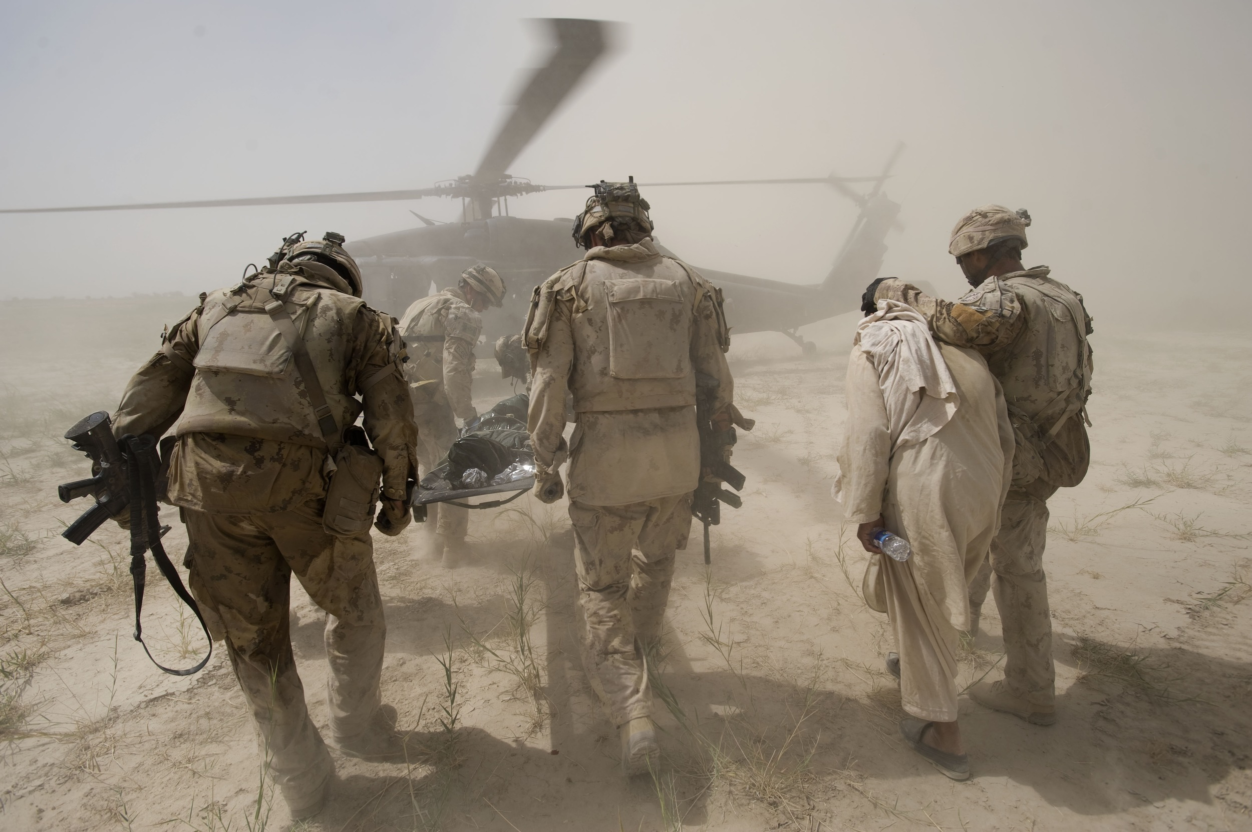 Canadian soldiers carry a critically wounded 8-year-old Afghan boy on a stretcher and escort his relative who will accompany him to a medevac helicopter after he was critically injured by an Improvised Explosive Device (IED) set by Taliban insurgents looking to target Canadian troops on patrol in the village of Fathullah in Panjwa'i District, Kandahar Province.Jul. 08, 2010 ©Louie Palu/Alexia Foundation/ZUMAPRESS.com