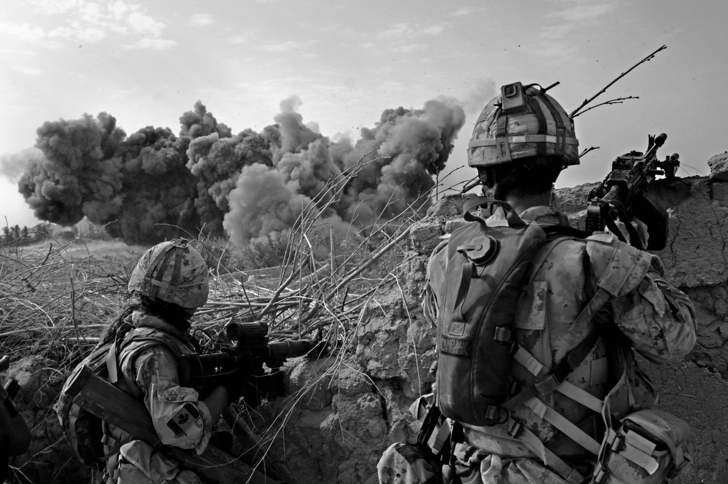 Canadian soldiers freeze and look in the direction of a massive air strike on an insurgent position just over 100 meters form their position during a heavy fighting in the vicinity of Pashmul in theZhari District, Kandahar Province, Afghanistan.July 27, 2008 © Louie Palu/ZUMAPRESS.com