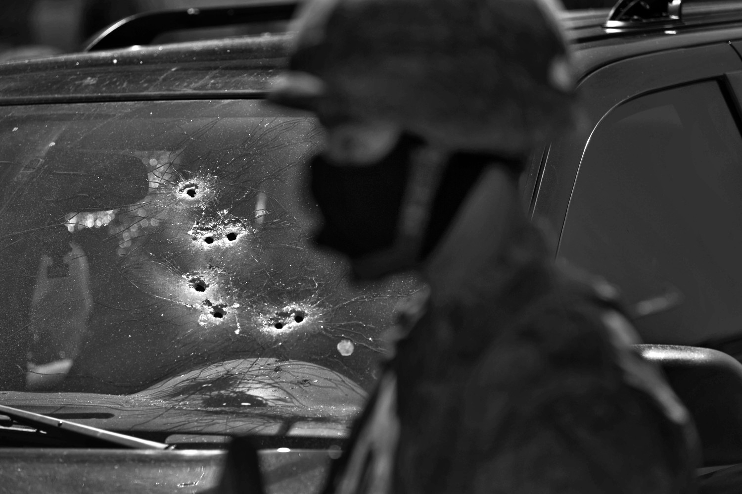 A Mexican soldier stands guard by a bullet riddled vehicle in which two men were executed by drug cartel assassins in Culiacan, Sinaloa, Mexico.March 2, 2012 ©Louie Palu/ZUMAPRESS.com