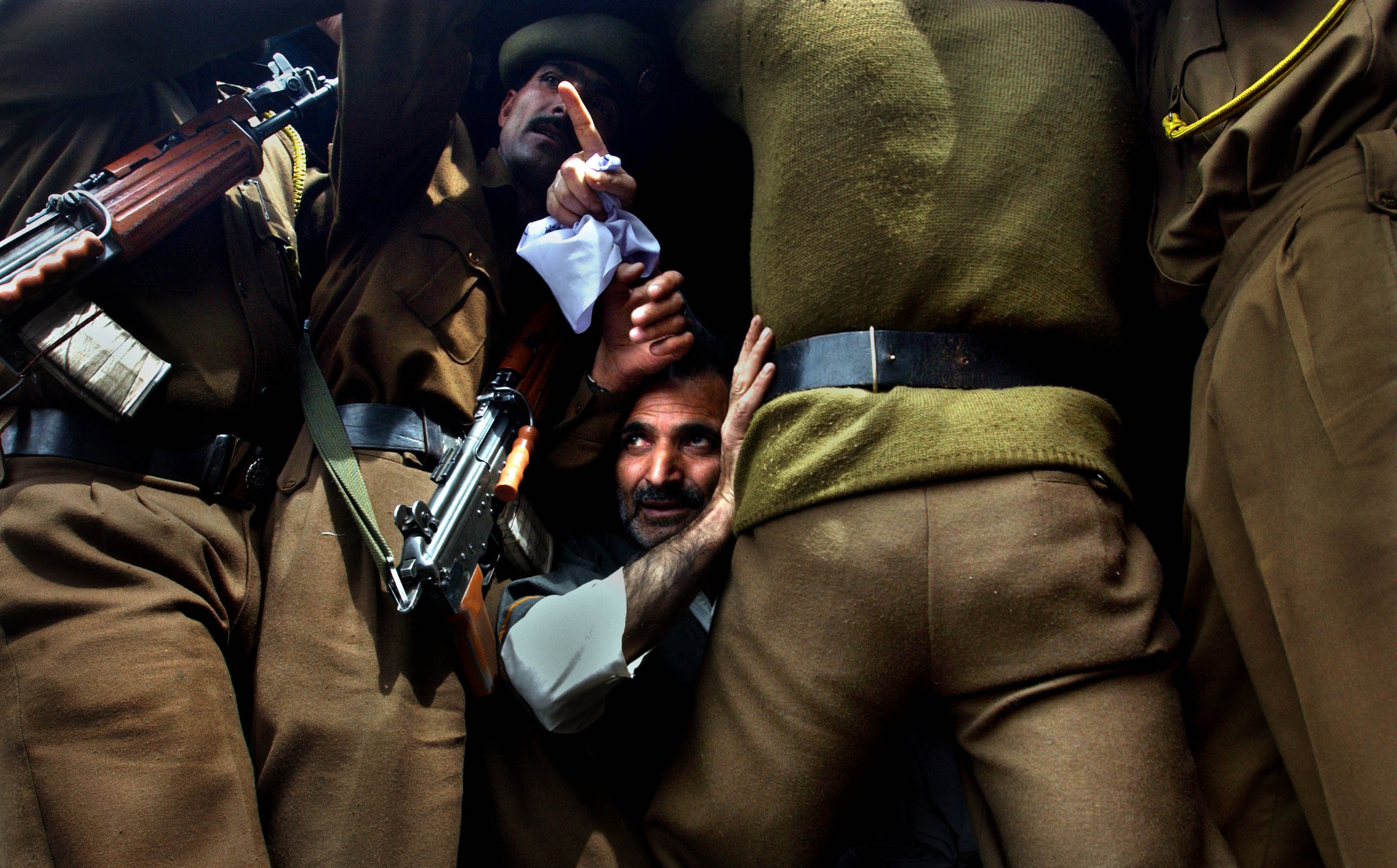 A Kashmiri  man sits inside a police van after he was arrested by Jammu and Kashmir police for protesting with the Association of Parents of Disappeared Persons (APDP) in Srinagar, the summer capital of Indian held Jammu and Kashmir state in India. 2004   © Ami Vitale