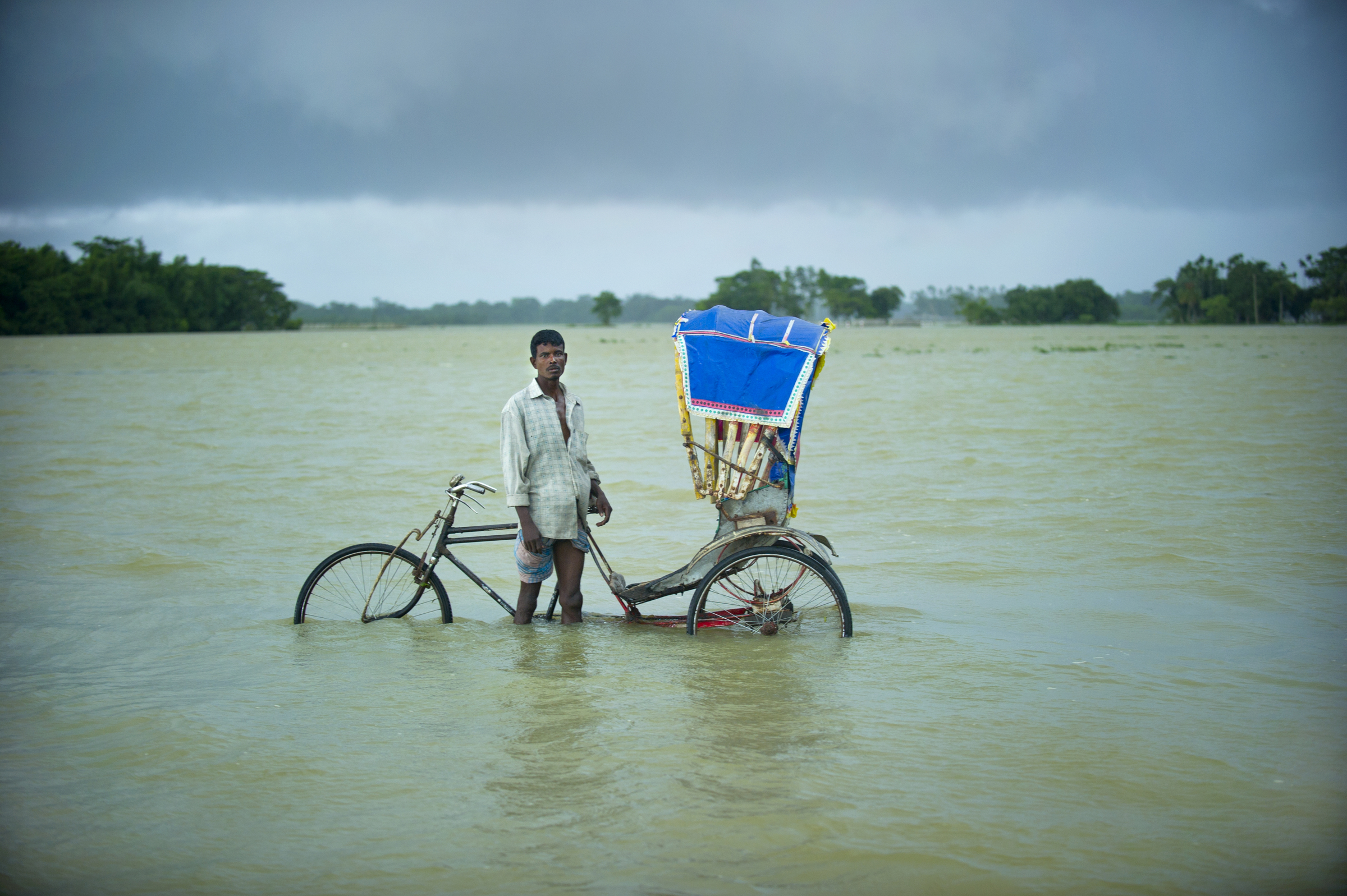 A rickshaw puller walks along a flooded road in Bangladesh. Scientists are predicting that climate change could lead to a rise in sea levels that would flood at least 17 percent of Bangladesh and create around 20-35 million refugees by 2050. 2010   © Ami Vitale