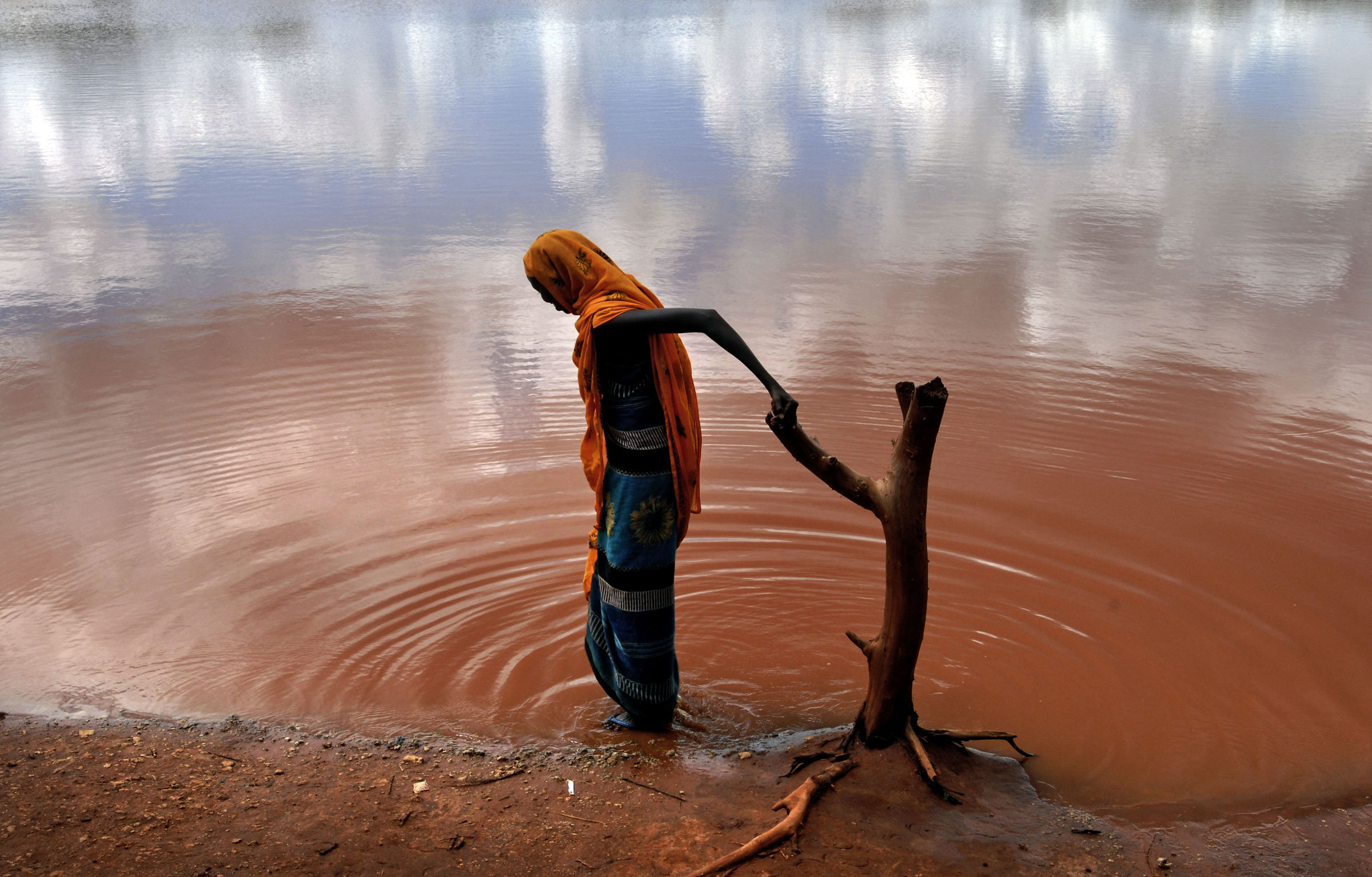 A villager fetches water from a polluted hole in the village of Dambas, 80 kilometers outside of Wajir, in northern Kenya. 2006   © Ami Vitale