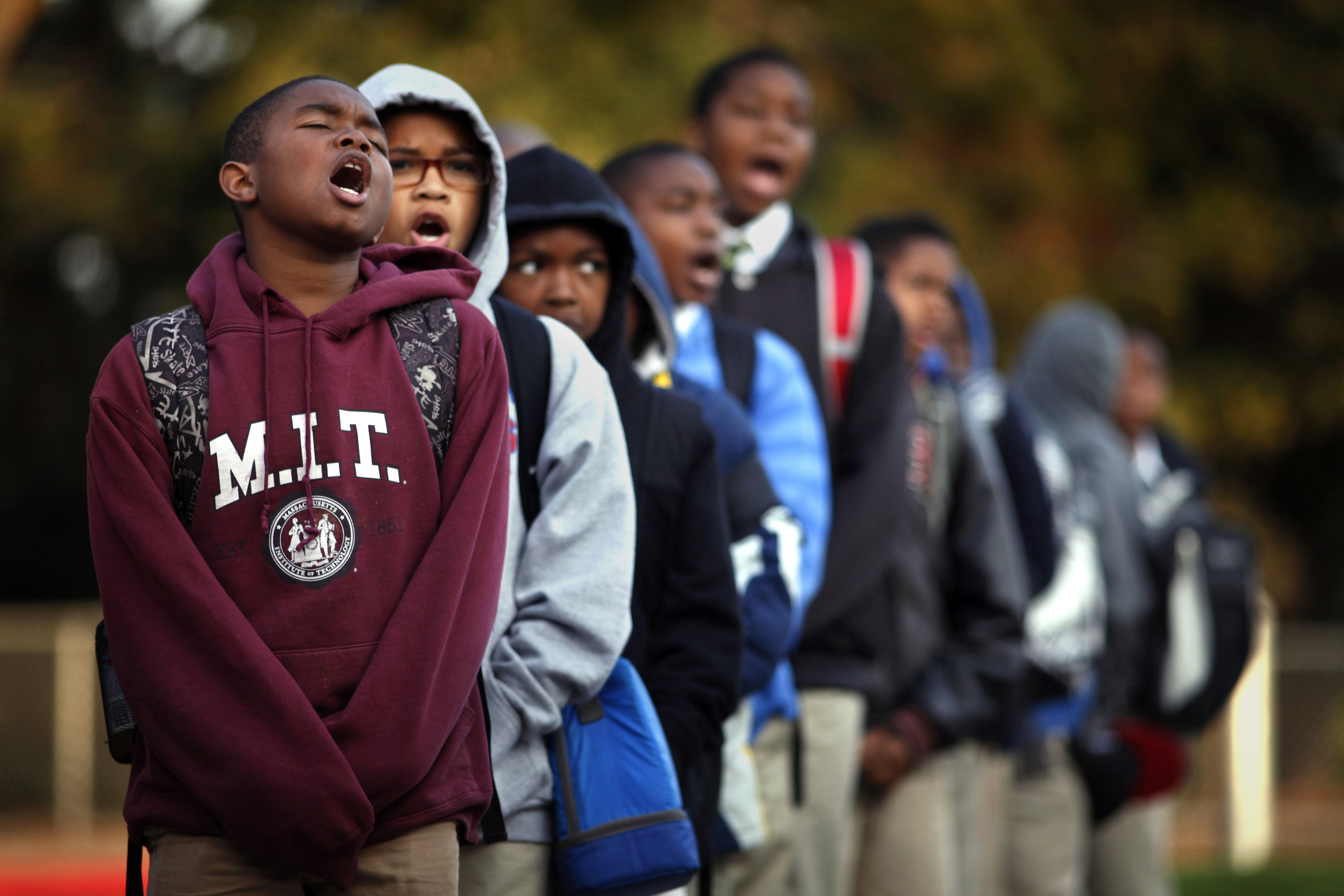 """Imir Stills-Bey, left, Donavon Richard and Kavion Hammond lead Mr. Peter Wilson's sixth-grade class in the """"scholar holler"""" at the start of school. The chant is done every morning before class at the 100 Black Men Community Charter School to promote a eagerness for learning.© Lacy Atkins/San Francisco Chronicle"""