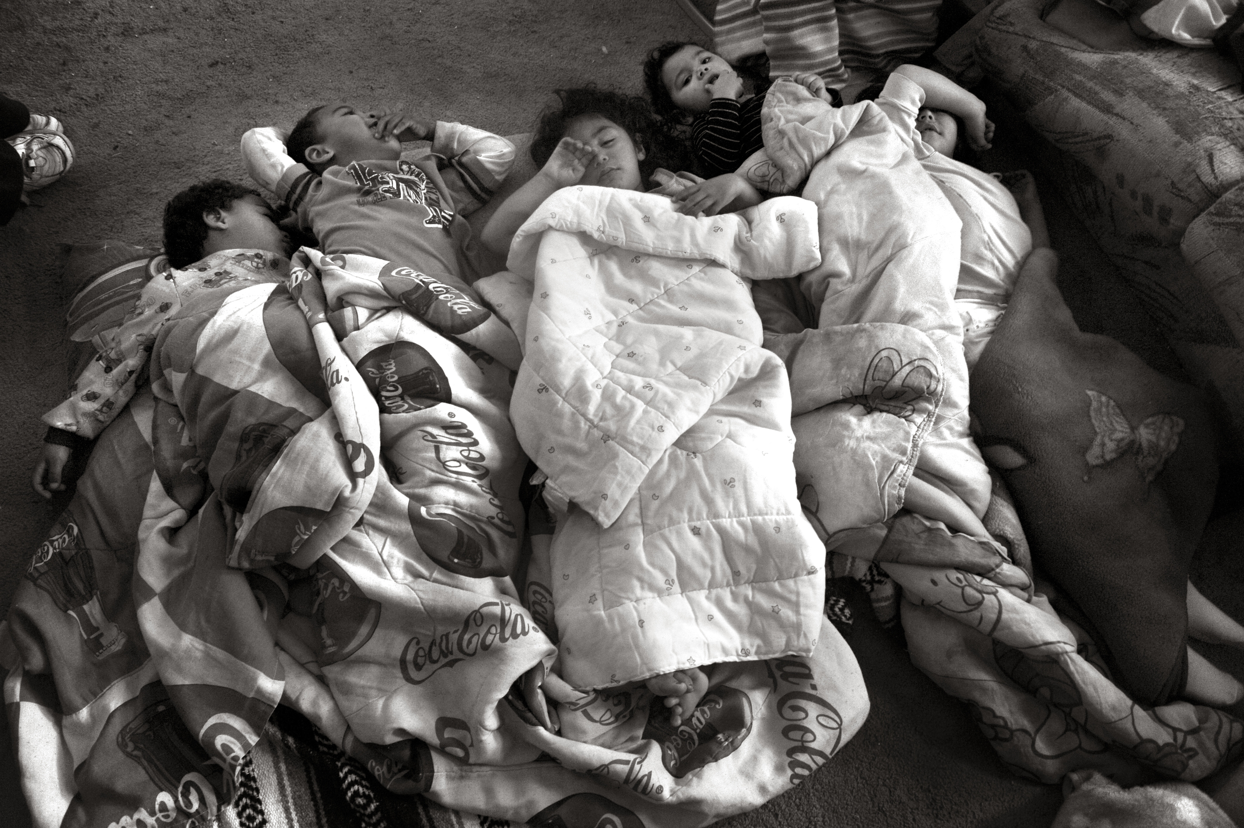 From left, Jamarion Atencio, Fai'zon Mitchell, Nia Atencio, Santiana Atencio and Nevaeh Atencio wake from their afternoon naps on the living room floor of the family home. © Reza A. Marvashti/The Denver Post