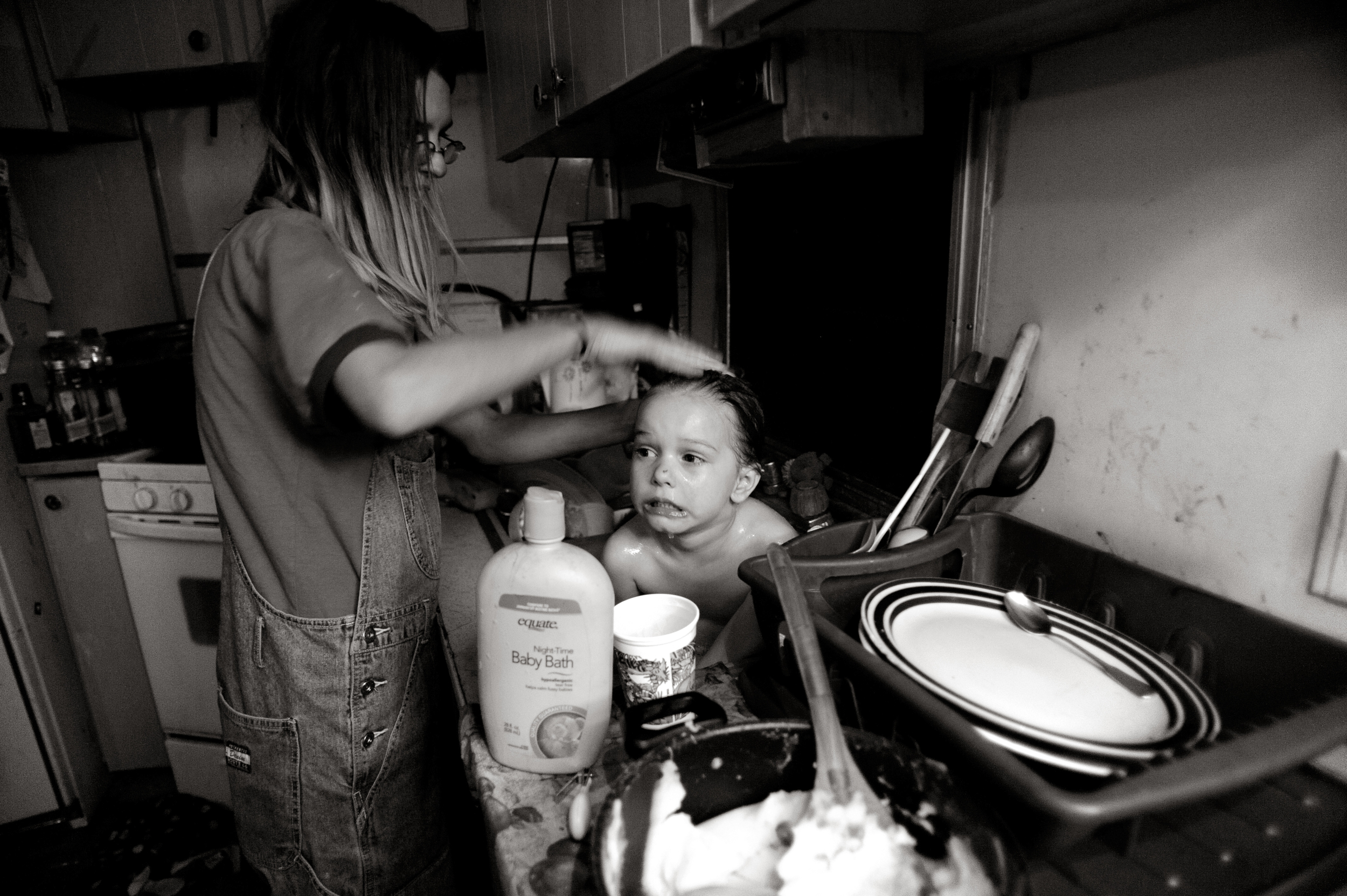 Charina Cook bathes her unwilling daughter, 3-year-old Lakota Vanessa Rene Douglas, in the kitchen sink. Cook and her children moved back in with her parents after her husband left them. © Joe Amon/The Denver Post