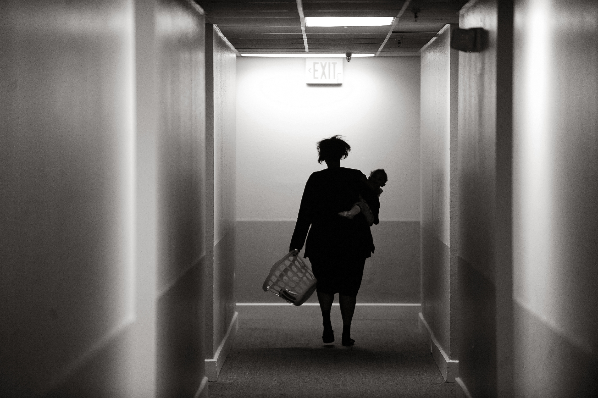 Shawnette Dorsey, 32, carries her baby girl, 13-month-old Shalisiana Fenwick, through the halls at Decatur Place apartments. Between trips to the laundry room, she was ironing clothes in preparation for church that morning.  © Craig F. Walker/The Denver Post