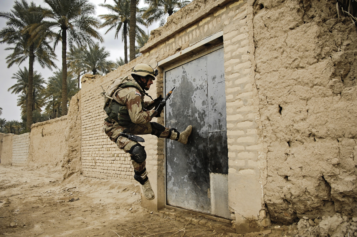 An Iraqi army soldier tries to kick open a gate during a cordon and search for insurgence and weapons caches in Chubinait, Iraq. 2007 © Stacy L. Pearsall