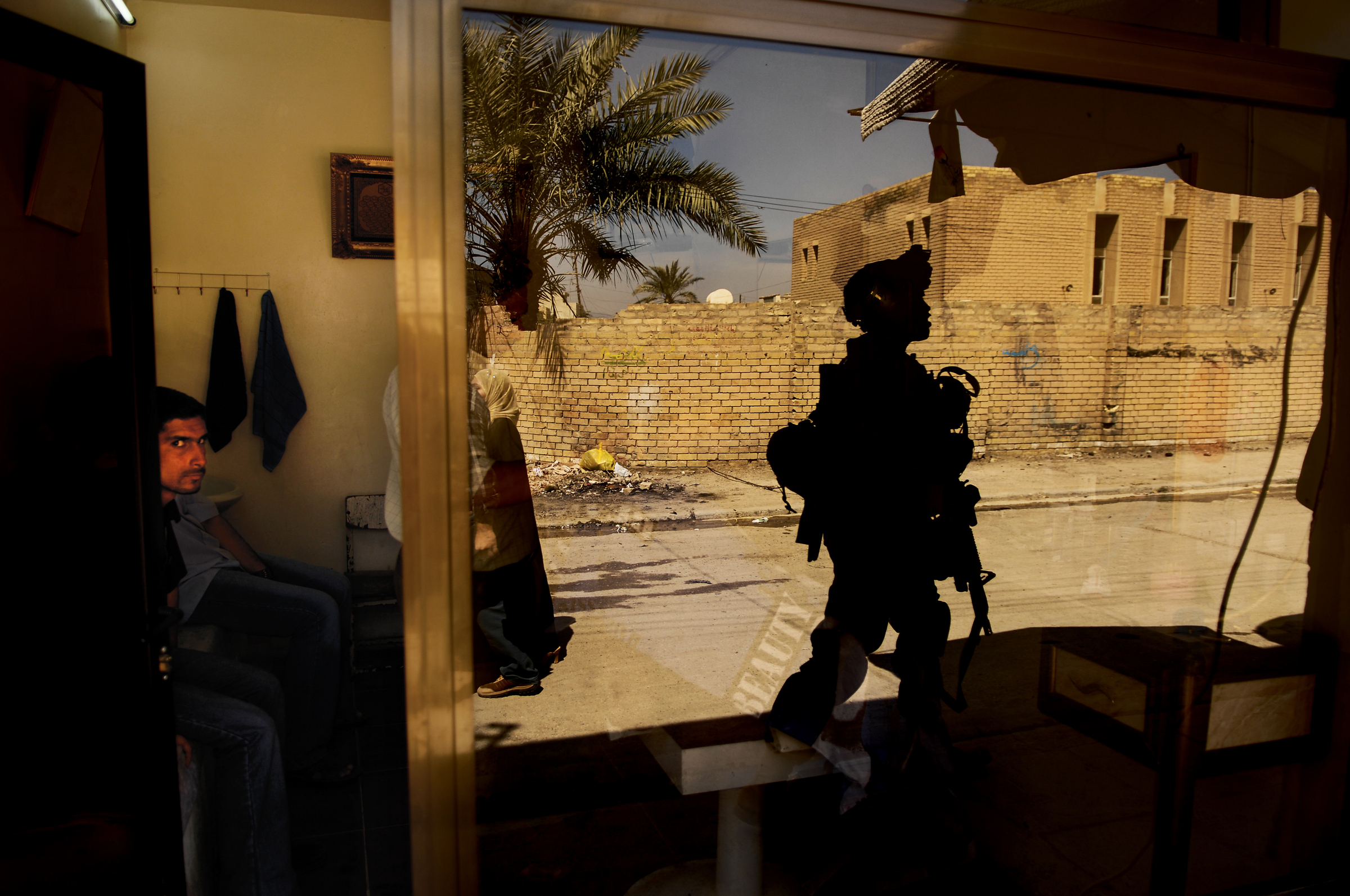 U.S. Army Pvt. 1st Class David Banks is eyed by locals as he walks past a barber shop during a cordon and search in Old Baqubah, Iraq. 2007 © Stacy L. Pearsall