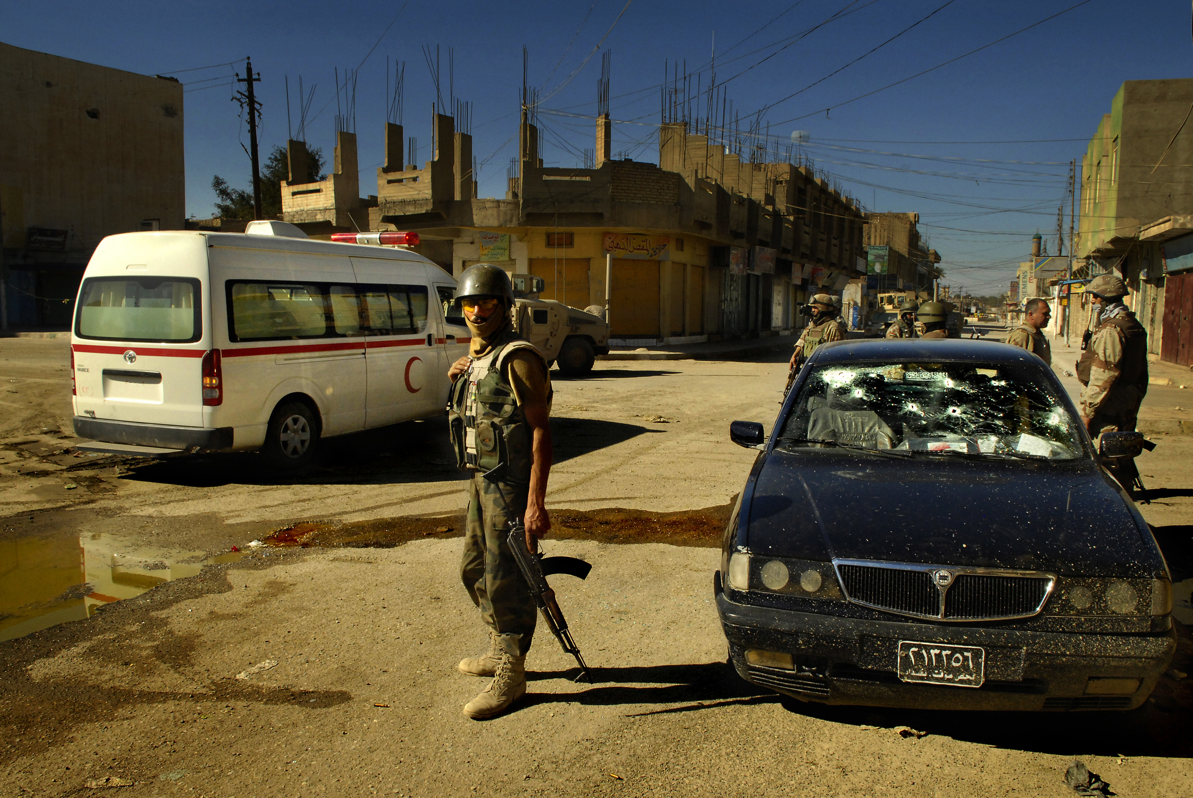 After shooting a fleeing insurgent's vehicle, members of the Iraqi army, 4th Battalion, 2nd Brigade, 5th Division, provide medical assistance to the car's occupants during an operation in Old Baqubah, Iraq. 2007 © Stacy L. Pearsall