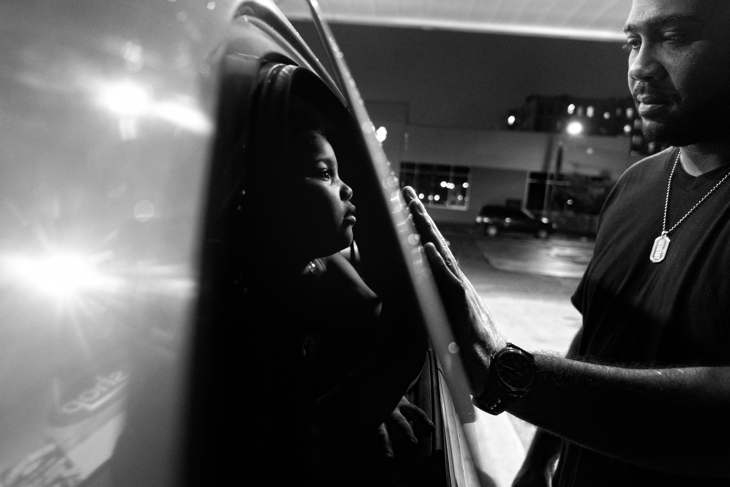 Blly Garcia shares a tender moment with daughter Esmeralda during a trip to the gas station. 2012 © Zun Lee