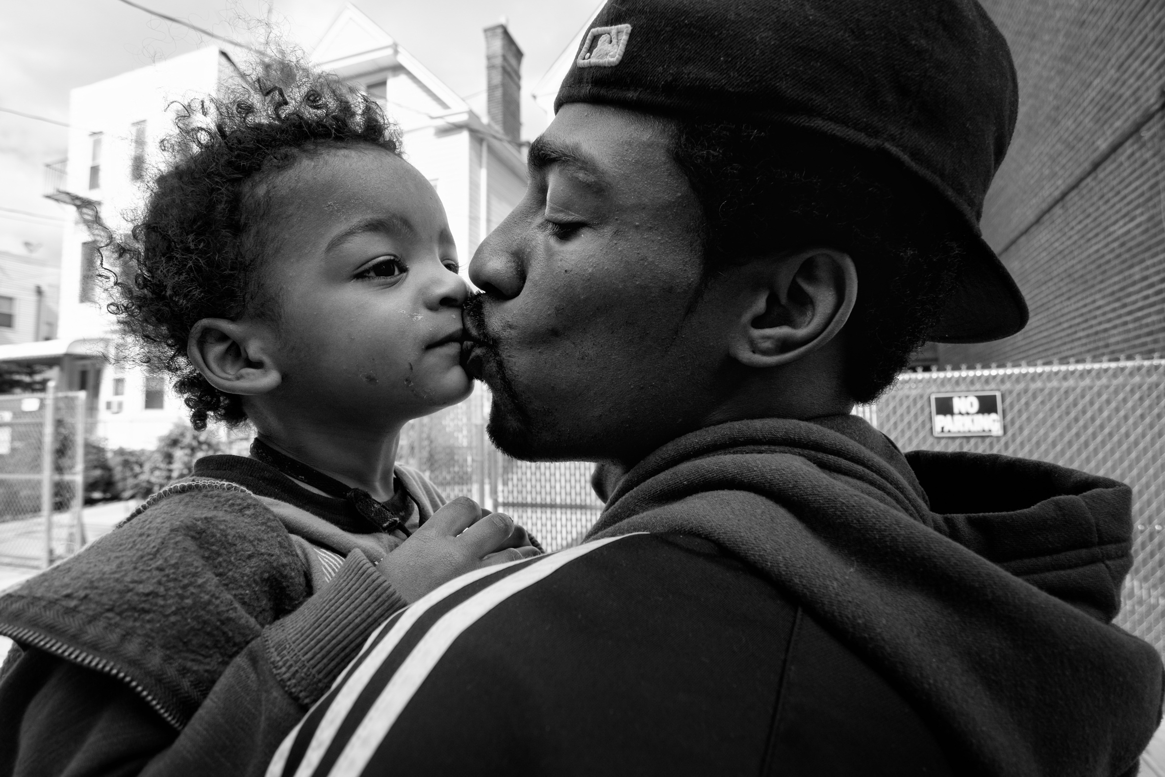"Guy Miller kisses his son ""Chum Chum"" while running daytime errands. Bronx, NY. 2013. © Zun Lee"