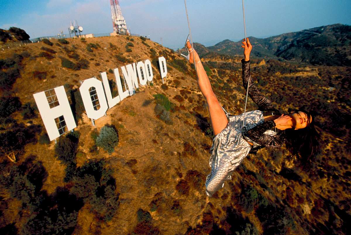 Michelle Yeoh, hangs from a helicopter over the Hollywood sign in California National Geographic 1998 © Joe McNally
