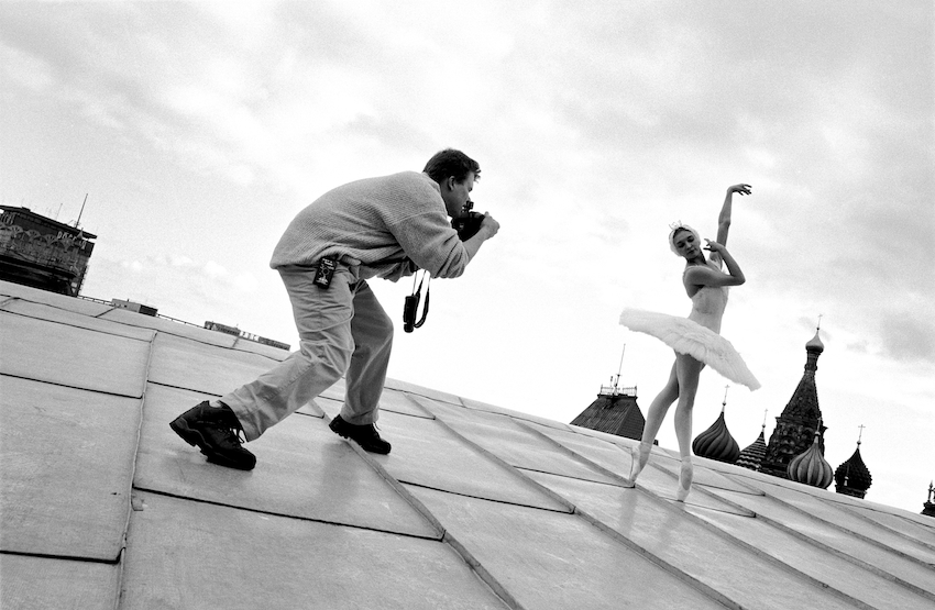 Joe McNally and Bolshoi prima ballerina Nadia Gracheva, balance themselves on a rooftop in Moscow 1997 © Joe McNally