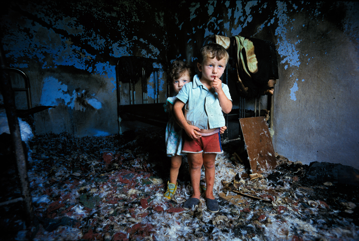 Chechen brother and sister peer from the room in their house which was bombed by Russian troops 1997 © Joe McNally