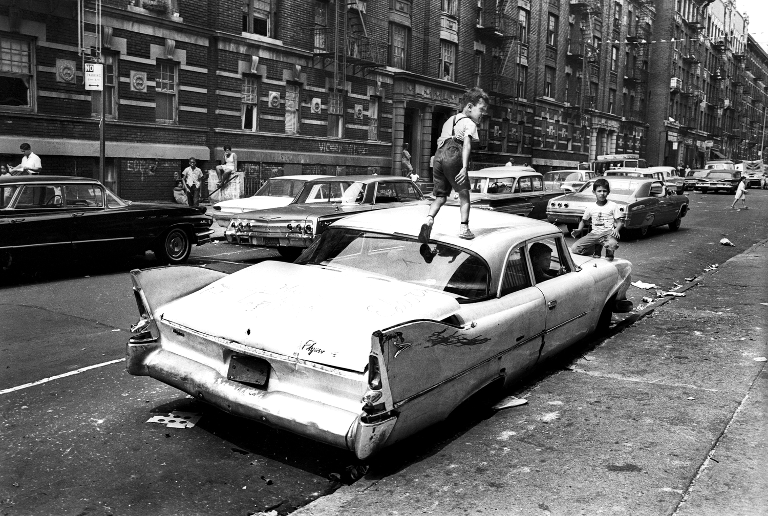 An abandoned car becomes a place for kids to play on Fox Street. From the mid-1960s to the late-1970s, the quality of life for Bronx residents declined sharply. Summer, 1966 © Jean-Pierre Laffont