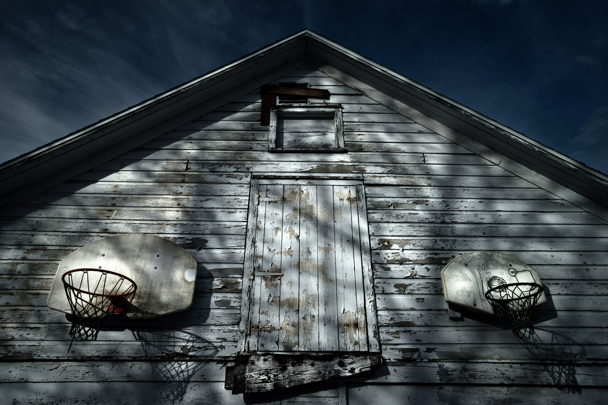 Two basketball hoops hang on an old barn in upstate New York © Rob Hammer