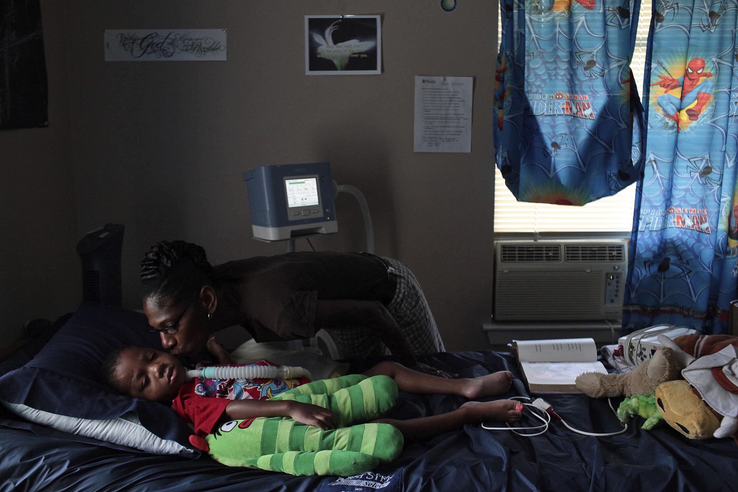 Rhodena Matthews, kisses her grandson, Braylon Nelson, 2, who was paralyzed in a road rage accident, at his home in San Antonio. © Lisa Krantz/San Antonio Express-News/ZUMA Press