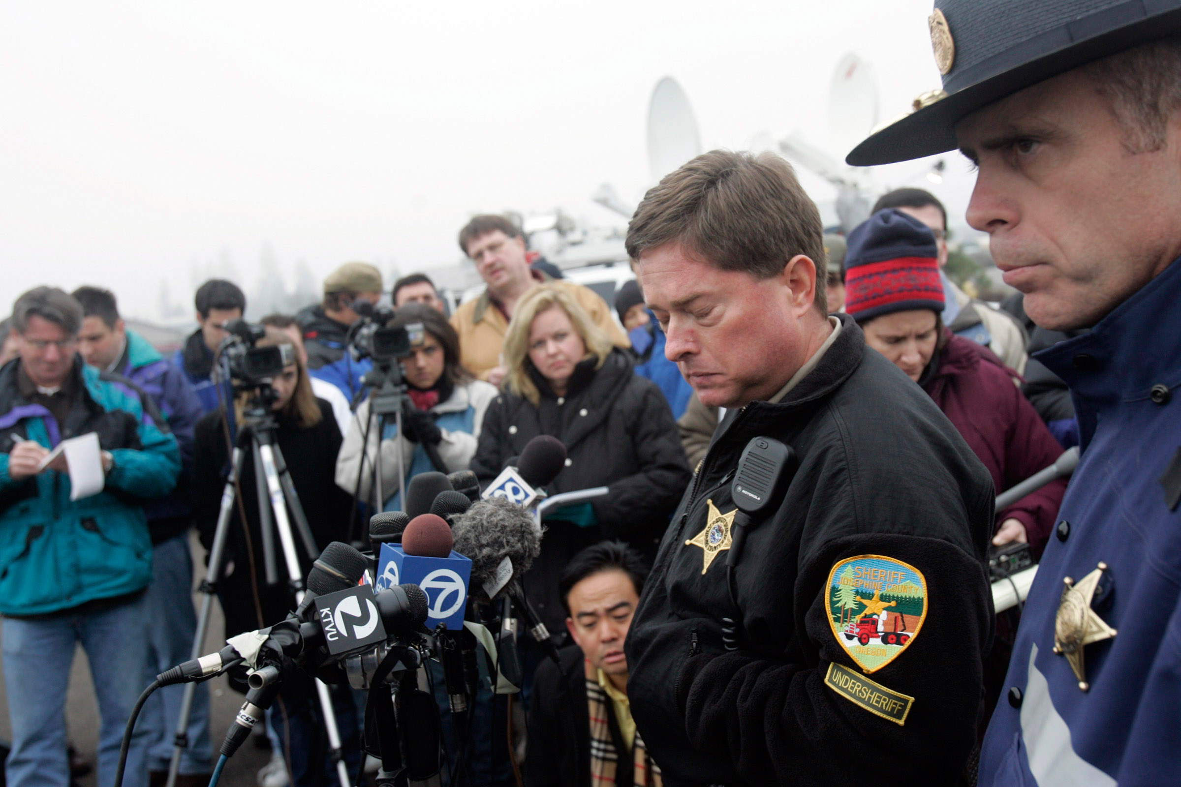 Josephine County Undersheriff Brian Anderson (center) and Oregon State Police Lt. Gregg Hastings soberly talk in more detail about thediscovery of the body of James Kim, 35, of San Francisco. Kim had tried to walk for help deep in the rugged Siskiyou National Forest. Part of the 2007 Pulitzer package.© Sol Neelman/The Oregonian