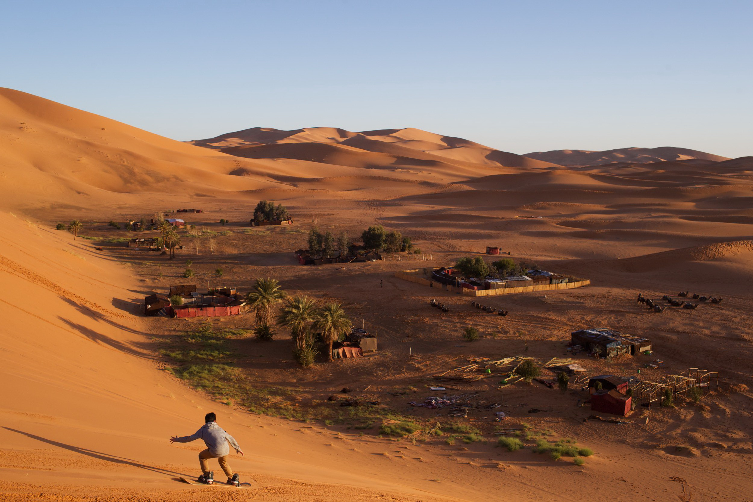 A Chinese tourist in the dunes of the Sahara Desert tries his hand at sandboarding for the first time during an overnight camping trip with classmates. 2nd place POYi this year, Recreational Sports.© Sol Neelman
