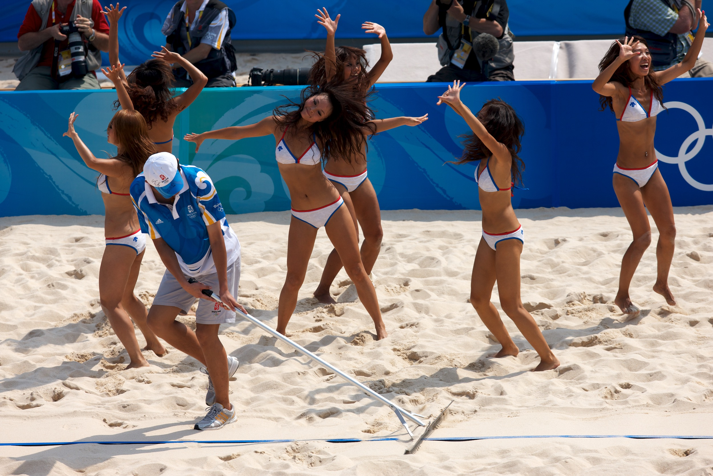 One of about 75,000 Chinese volunteers sweeps a sand court during a beach volleyball match as cheerleaders - many of them trained by their American counterparts - entertain the crowd.© Sol Neelman