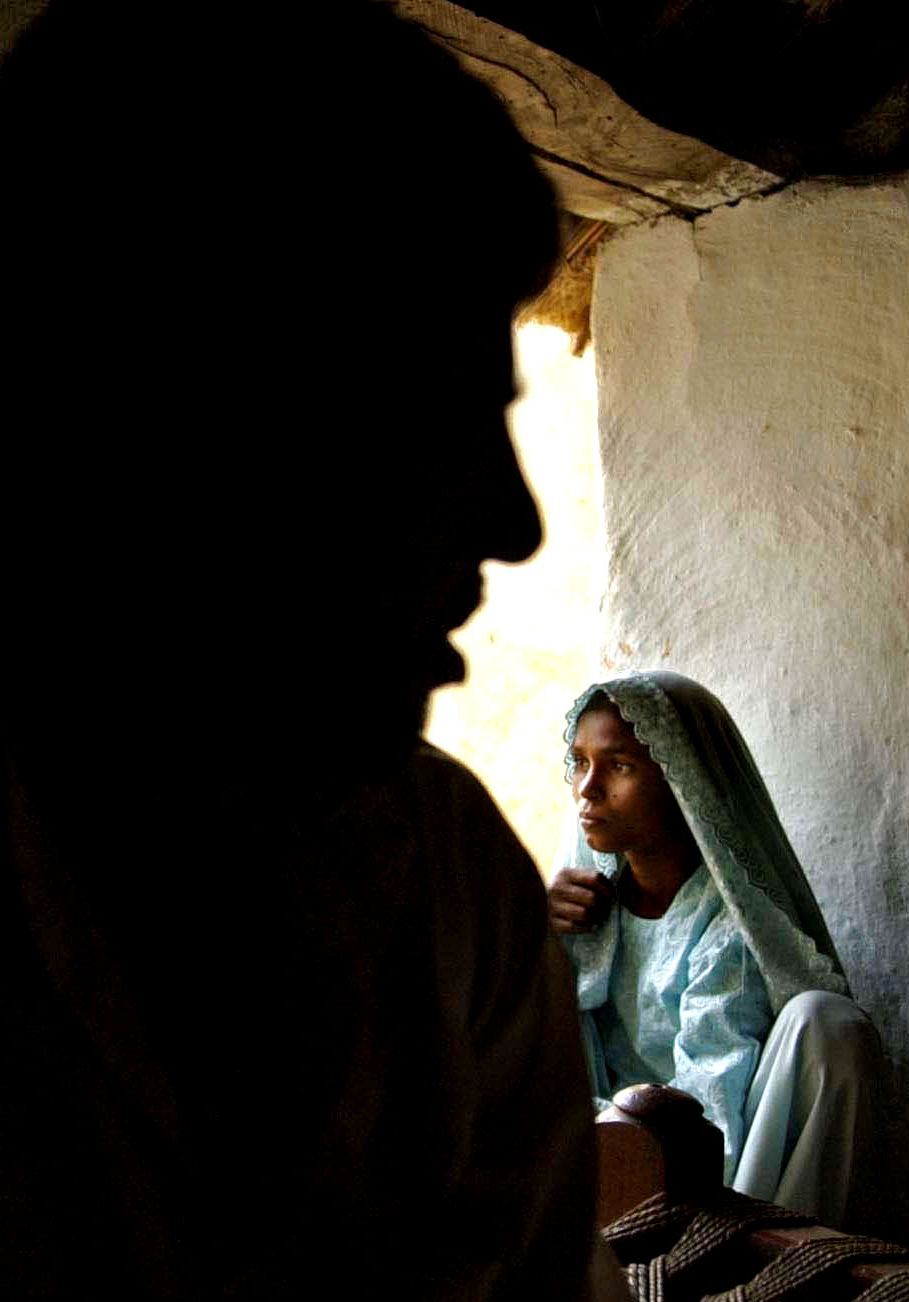 India's Lost Daughters:     Rakshana Begum, right, squats in a corner of her house in the shadow of her husband.     © Mary F. Calvert/The Washington Times/ ZUMAPRESS.com