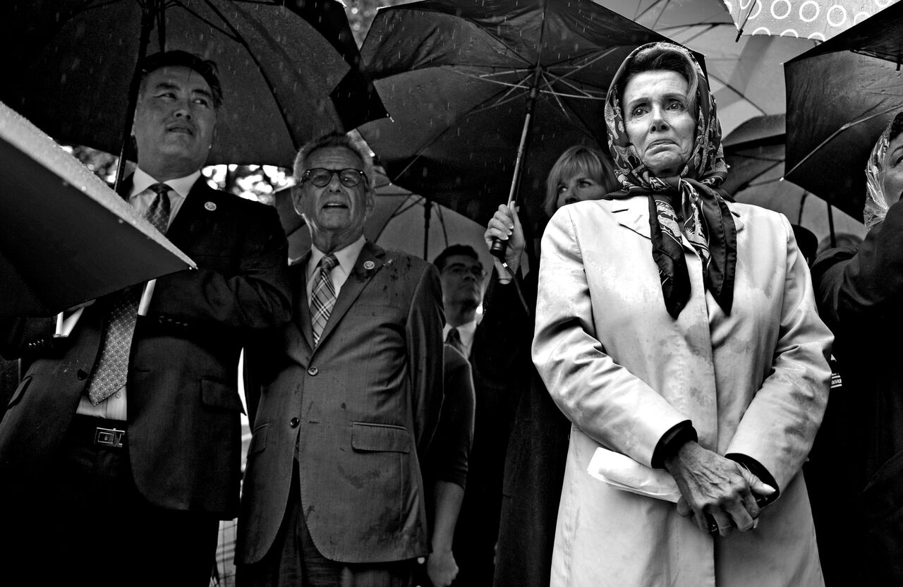 "House Minority Leader Nancy Pelosi stands in the pouring rain after addressing the crowd at the ""Stop the Lockout"" rally at Upper Senate Park in Washington DC.  © Mary F. Calvert/ ZUMAPRESS.com"