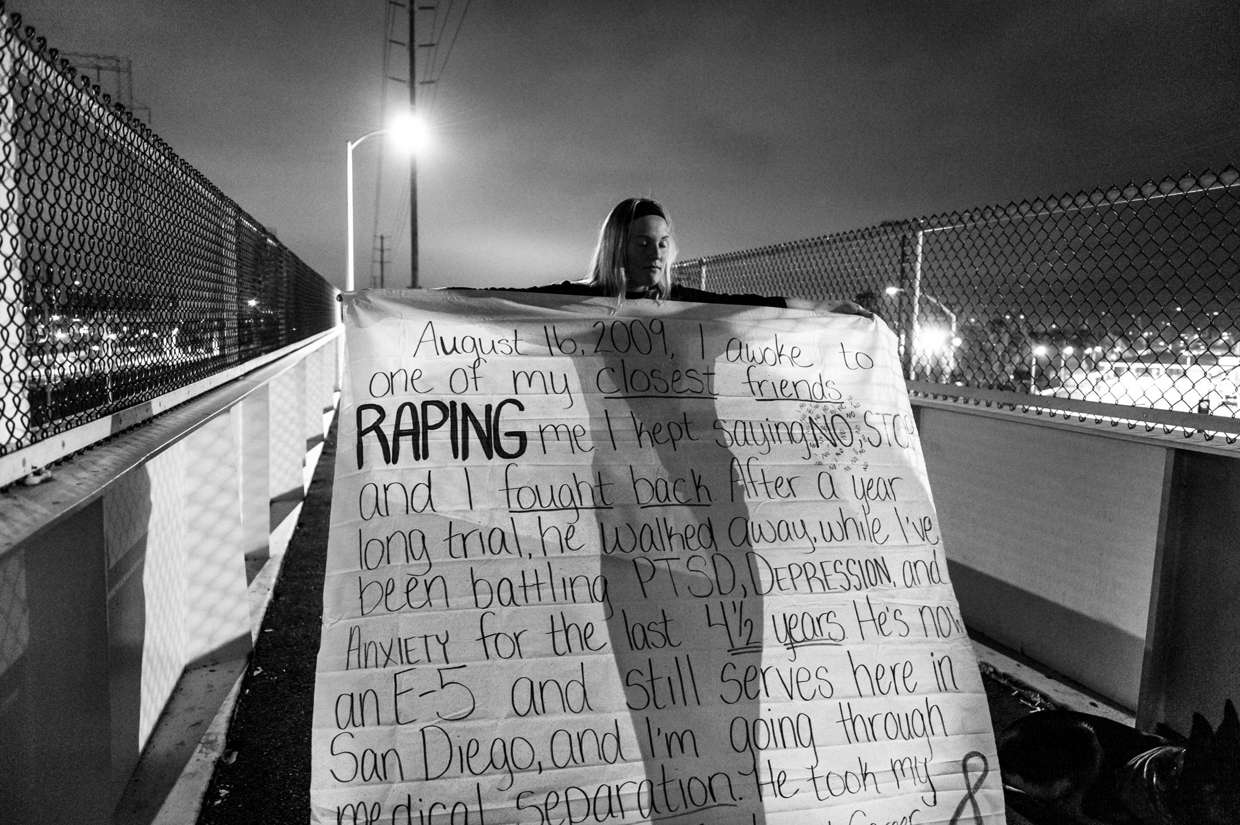 The War Within: Melissa Bania holds her banner, before hanging it on the foot bridge across from the entrance to Naval Station San Diego. US Navy Military Sexual Trauma survivors got together to make banners inscribed with their sexual assault experiences in the US Navy.  © Mary F. Calvert/ ZUMAPRESS.com