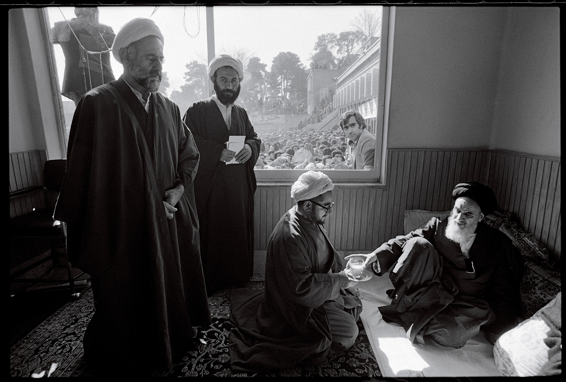 """Ayatollah Khomeini is served tea in his room at the Refah School by Sadegh Khalkhali, who later became known as """"the hanging judge."""" Tehran, February 5, 1979.© 2015 David Burnett/Contact Press Images"""