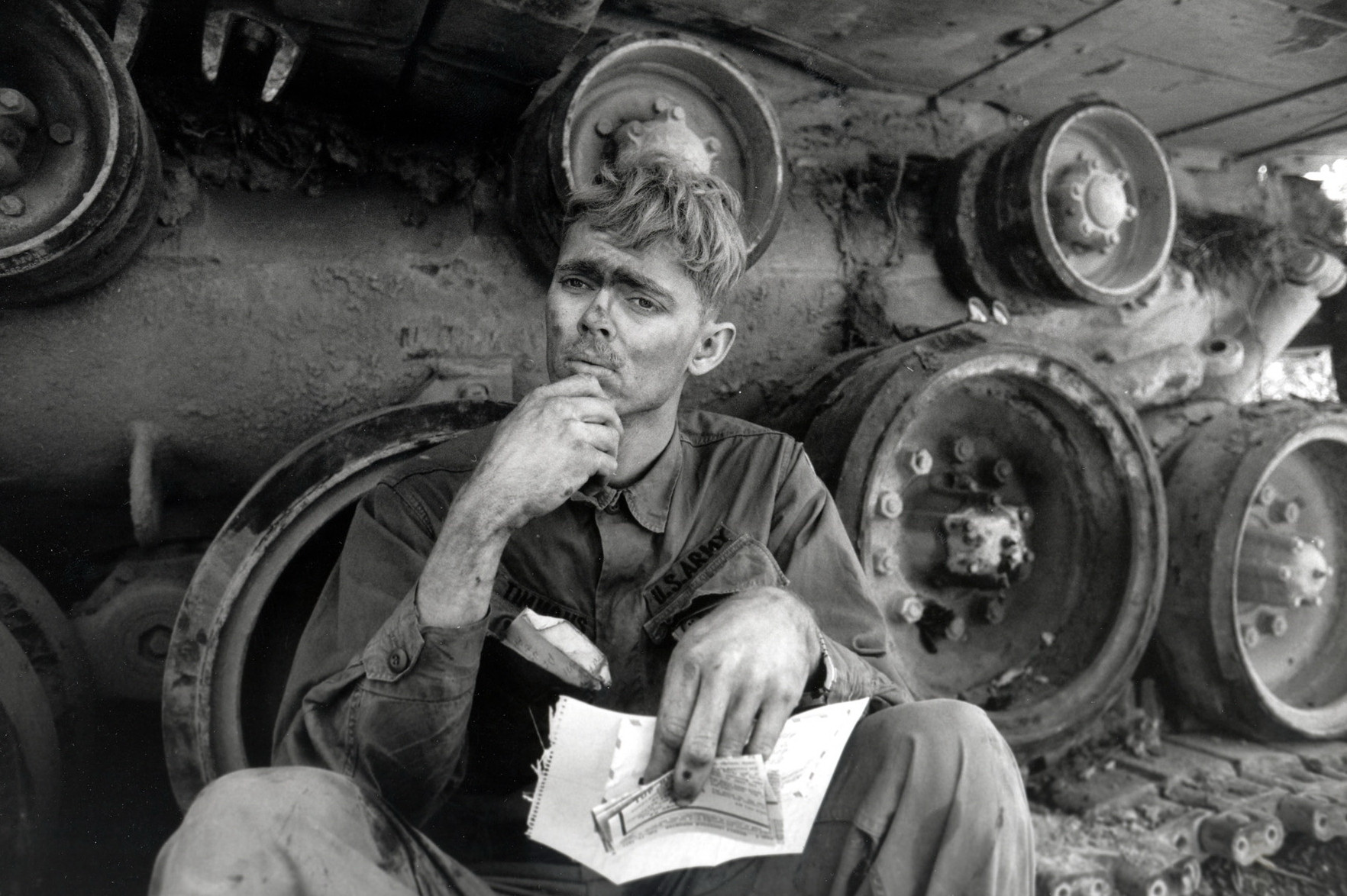 An American soldier reads a letter from home, while taking a break from repairing a tank tread. Lang Vei, South Vietnam, March 1971 © 2015 David Burnett/Contact Press Images