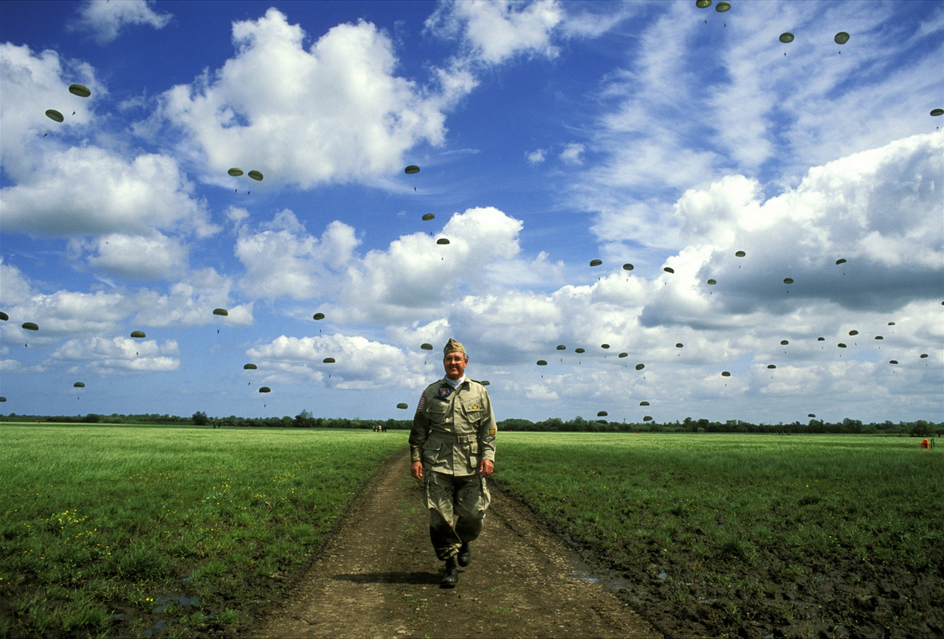 In 1994, on occasion of the 50th anniversary of D Day, Robert L Williams, 101st Airborne trooper, jumped with a bunch of former vets at Ste Mere Eglise. The sky behind is filled with chutes of active duty troops who jumped just after the vets did. © 2015 David Burnett/Contact Press Images