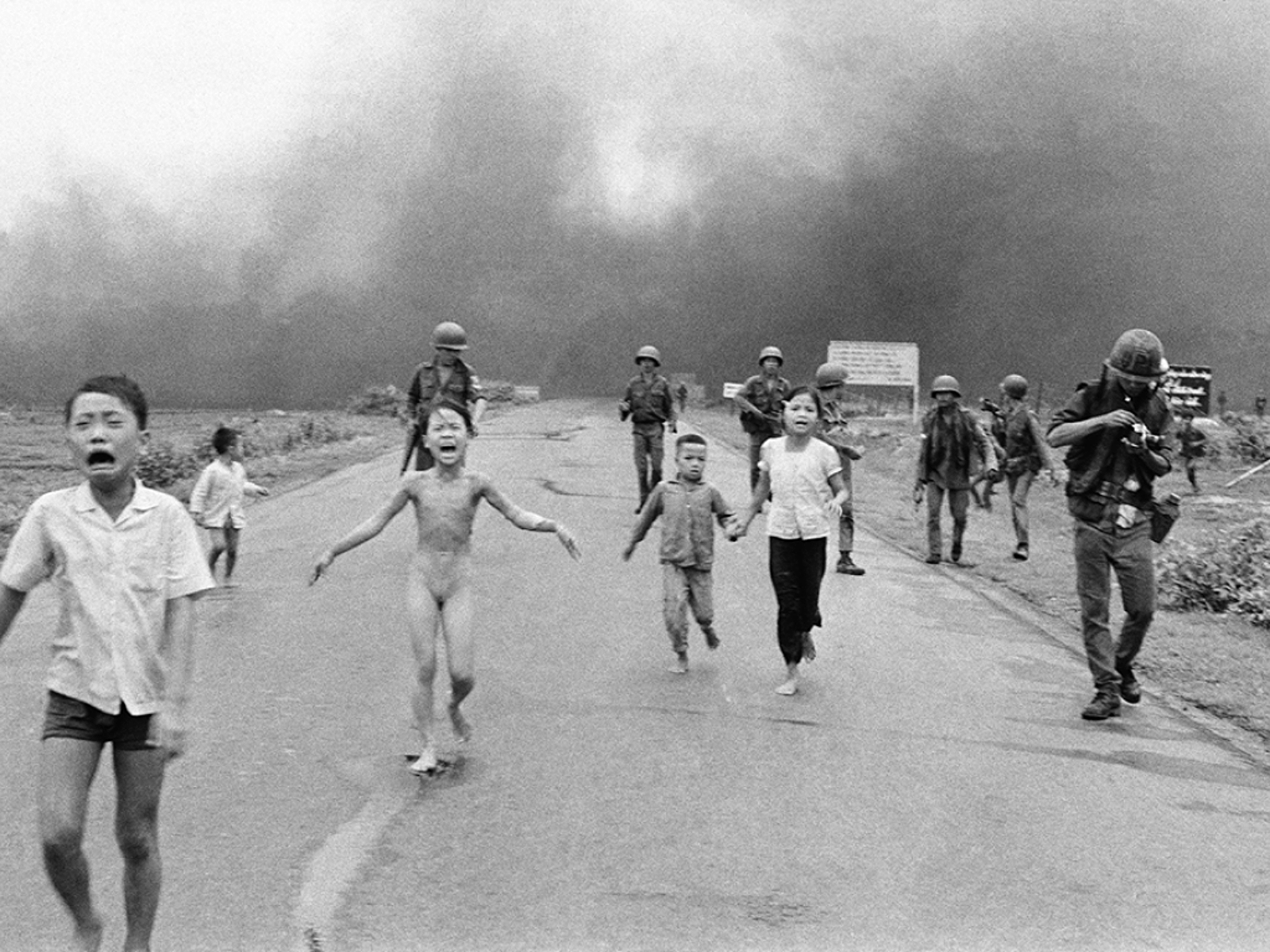 Trang Bang, Vietnam, June 8, 1972: 9-year-old Kim Phuc runs naked in the street after a napalm attack. One of David Burnett's images from that fateful day is included in the gallery.© Nick Ut/AP
