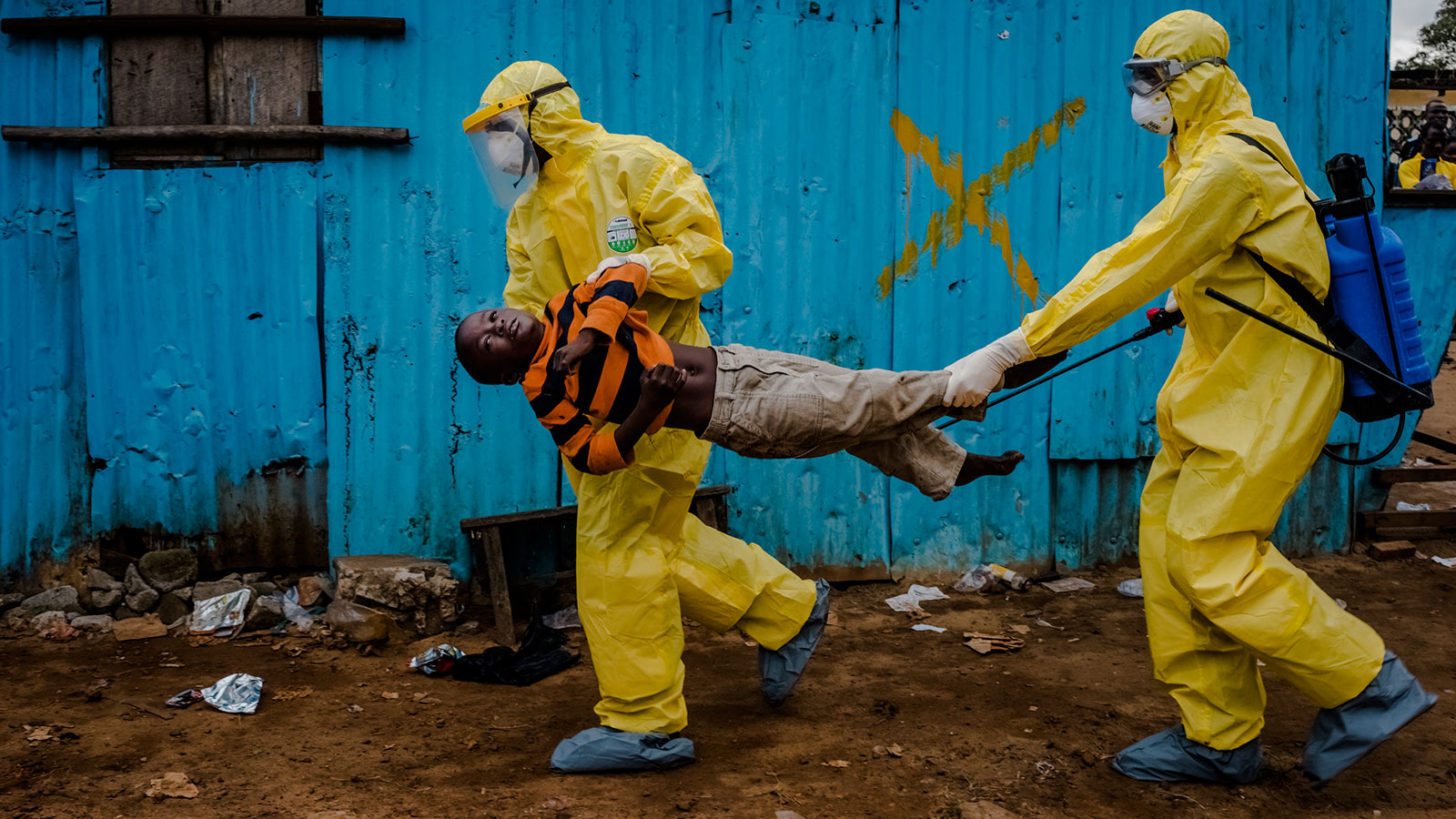 James Dorbor, 8, suspected to have Ebola, is rushed by medical staff wearing protective clothing into the JFK Ebola treatment center in Monrovia, Liberia. James passed away shortly after being admitted that same day. September 05, 2014  © Daniel Berehulak for The New York Times