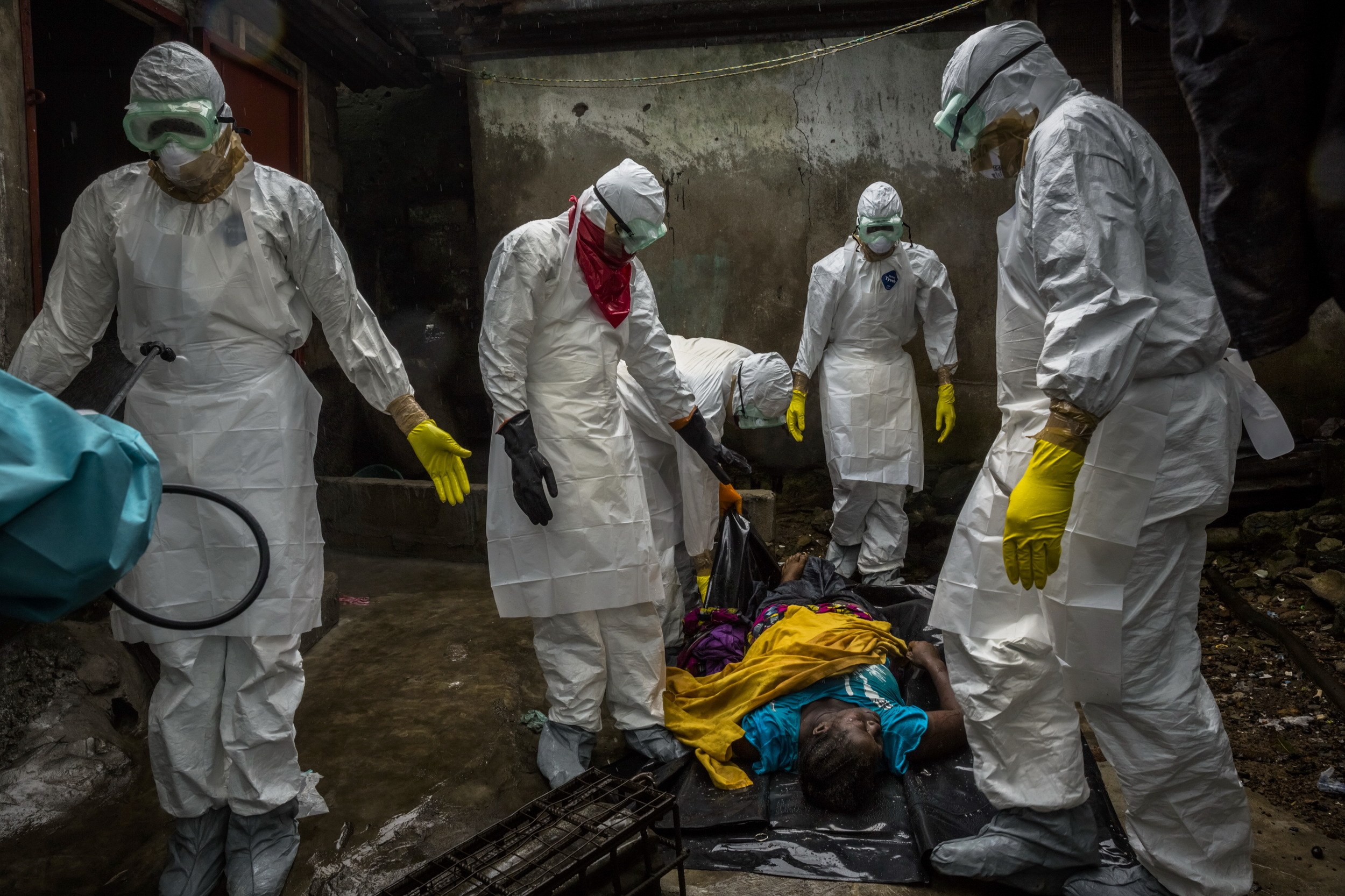 Members of a Liberian Red Cross burial team, under contract from the Liberian Ministry of Health, remove the body of a suspected Ebola victim Lorpu David, 30 in the Gurley street community in central Monrovia, Liberia. September 18, 2014 © Daniel Berehulak for The New York Times