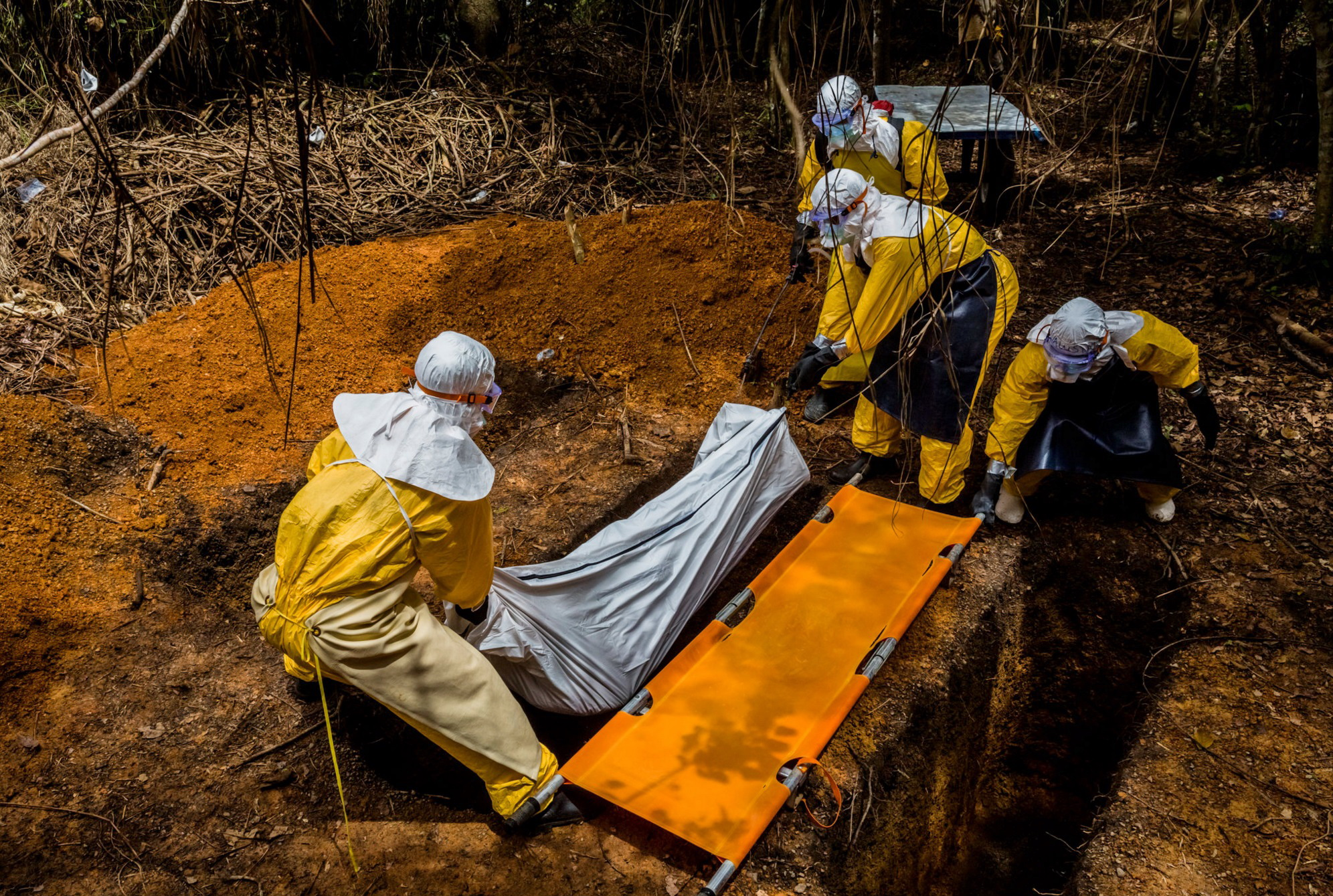A burial team transfer Ballah Kollie, 20, who lost his fight against Ebola yesterday, into his resting place in a graveyard adjacent to the Bong County Ebola Treatment Unit in Suakoko near Gbarnga in Bong County, Liberia. October 6, 2014 © Daniel Berehulak for The New York Times