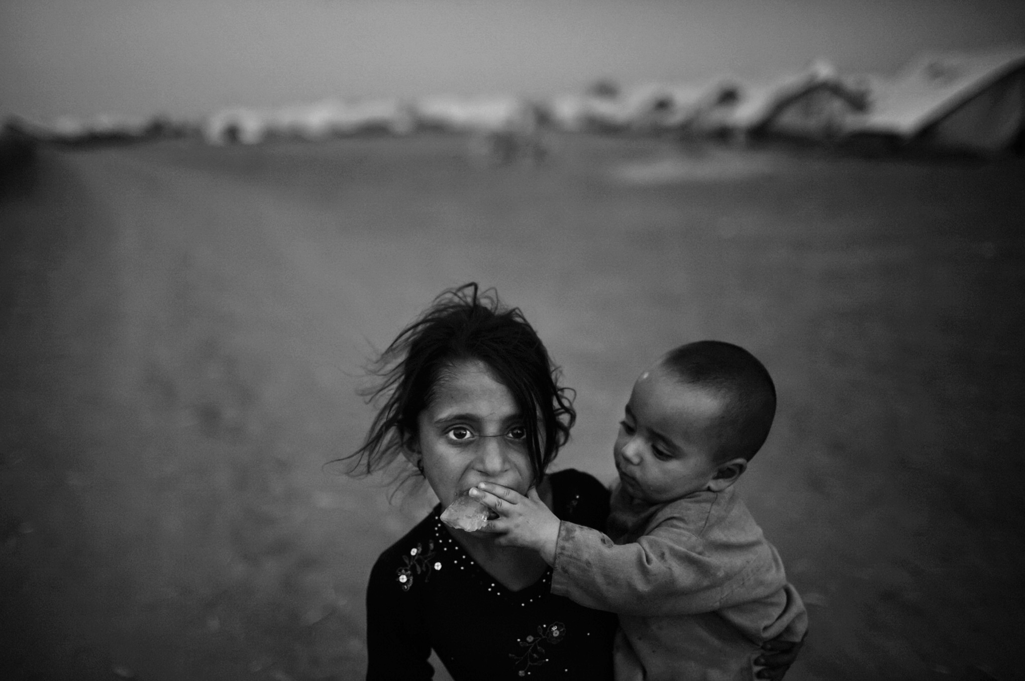 A young girl, internally displaced due to the Pakistan Army's offensive against the Taliban in Swat, looks on as her brother puts a block of ice in her mouth at the Chota Lahore relief camp in Swabi, Pakistan. May 20, 2009 © Daniel Berehulak/Getty Images